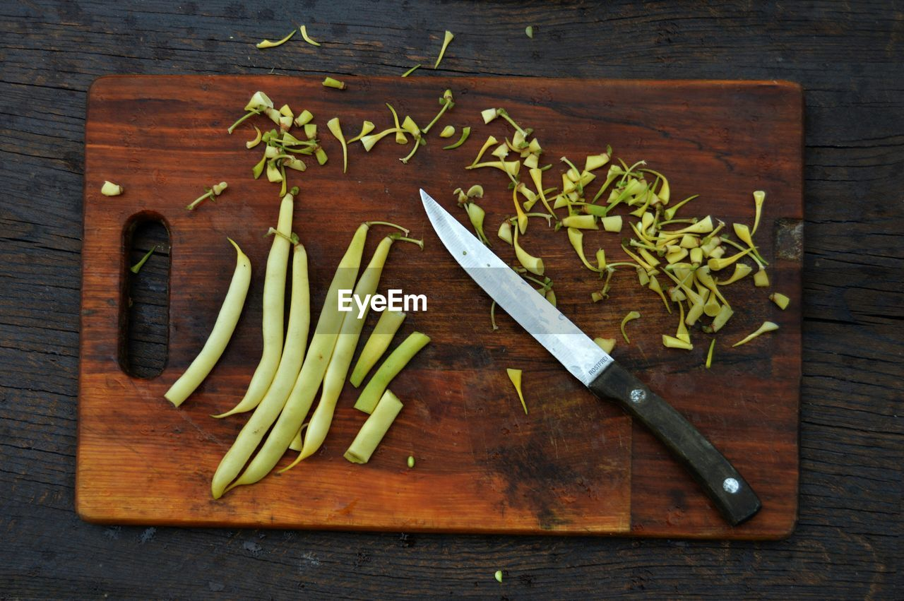 food and drink, wood - material, table, indoors, freshness, directly above, vegetable, food, healthy eating, still life, high angle view, no people, cutting board, wellbeing, knife, green color, kitchen knife, large group of objects, text, close-up, table knife, chopped, wood grain