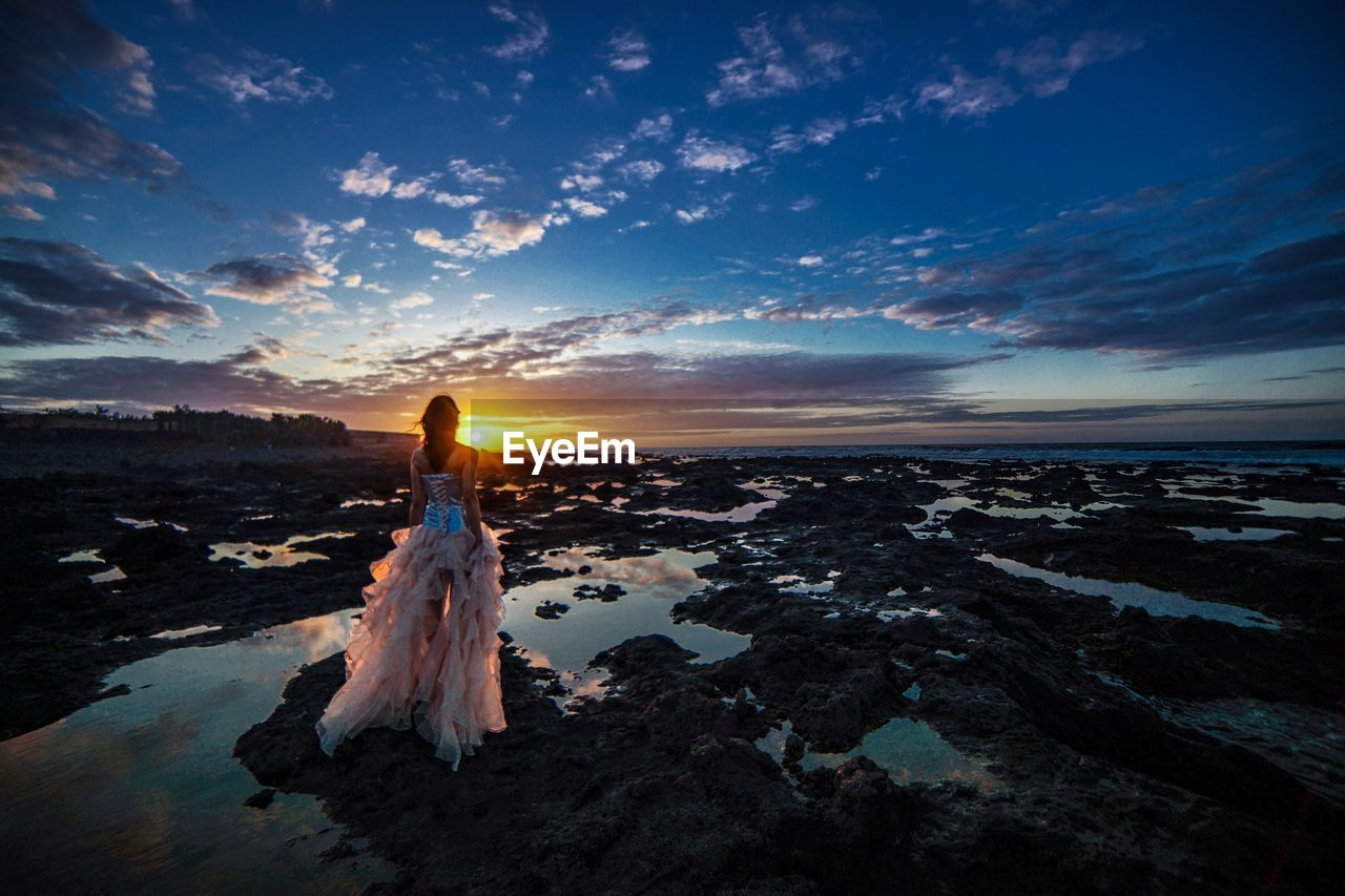 Woman standing on scenic sea against sky during sunset