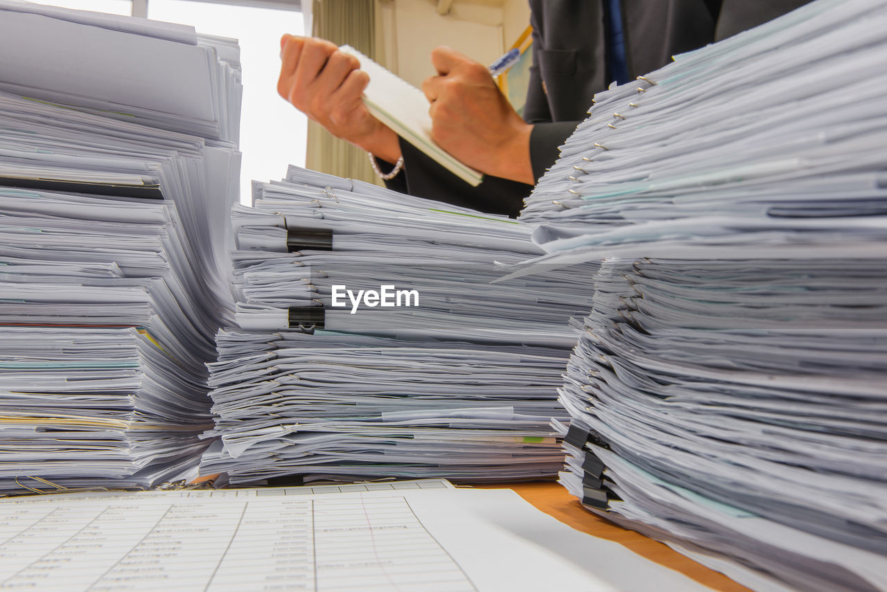 Stack of files on table with business person working in background
