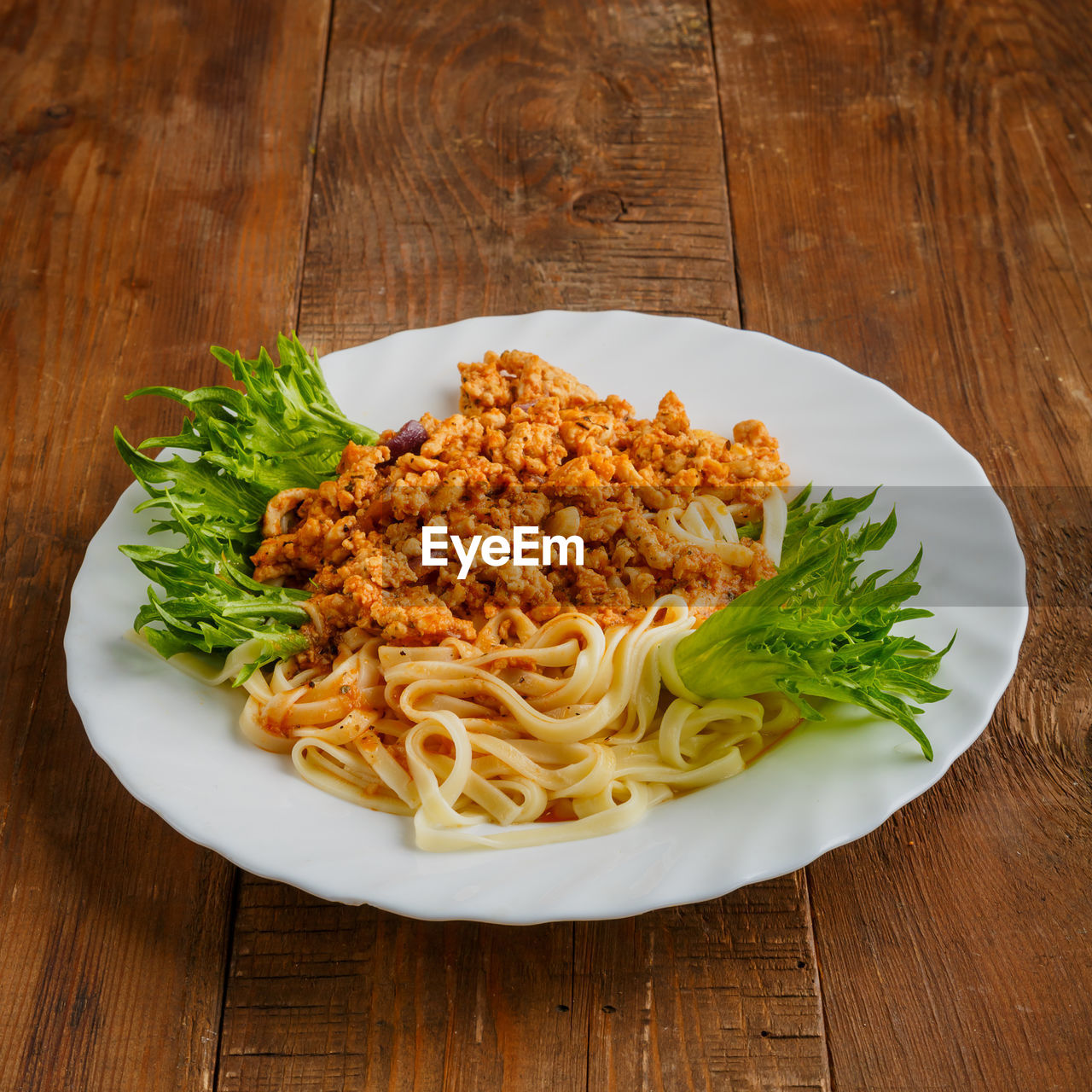 A plate of pasta in bolognese sauce on a wooden table. vertical photo