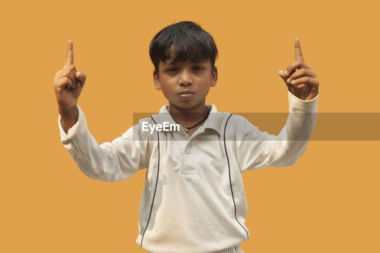 FULL LENGTH PORTRAIT OF BOY STANDING AGAINST GRAY BACKGROUND