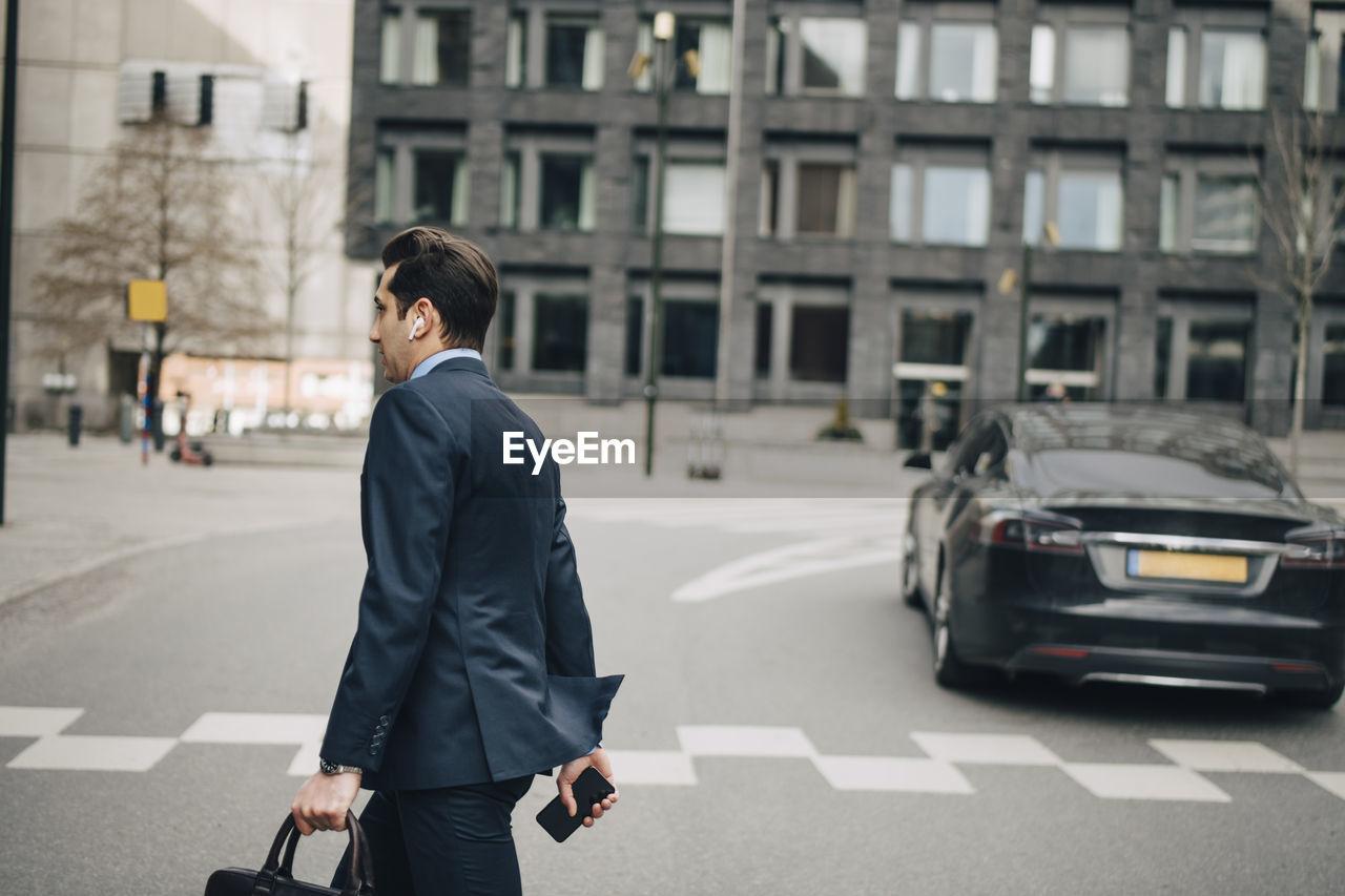 FULL LENGTH REAR VIEW OF MAN WALKING ON STREET IN CITY