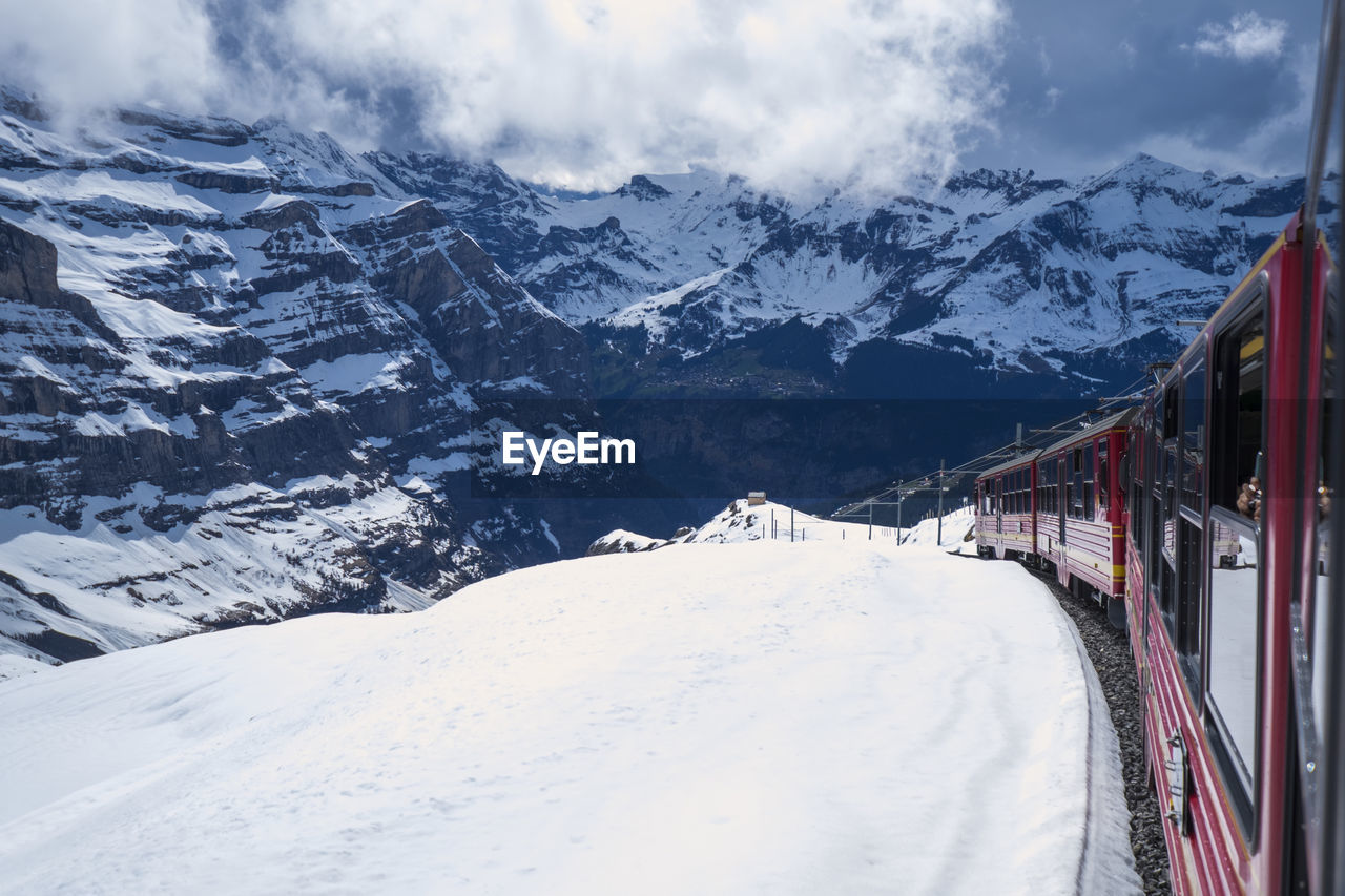Train On Snowcapped Mountains Against Cloudy Sky