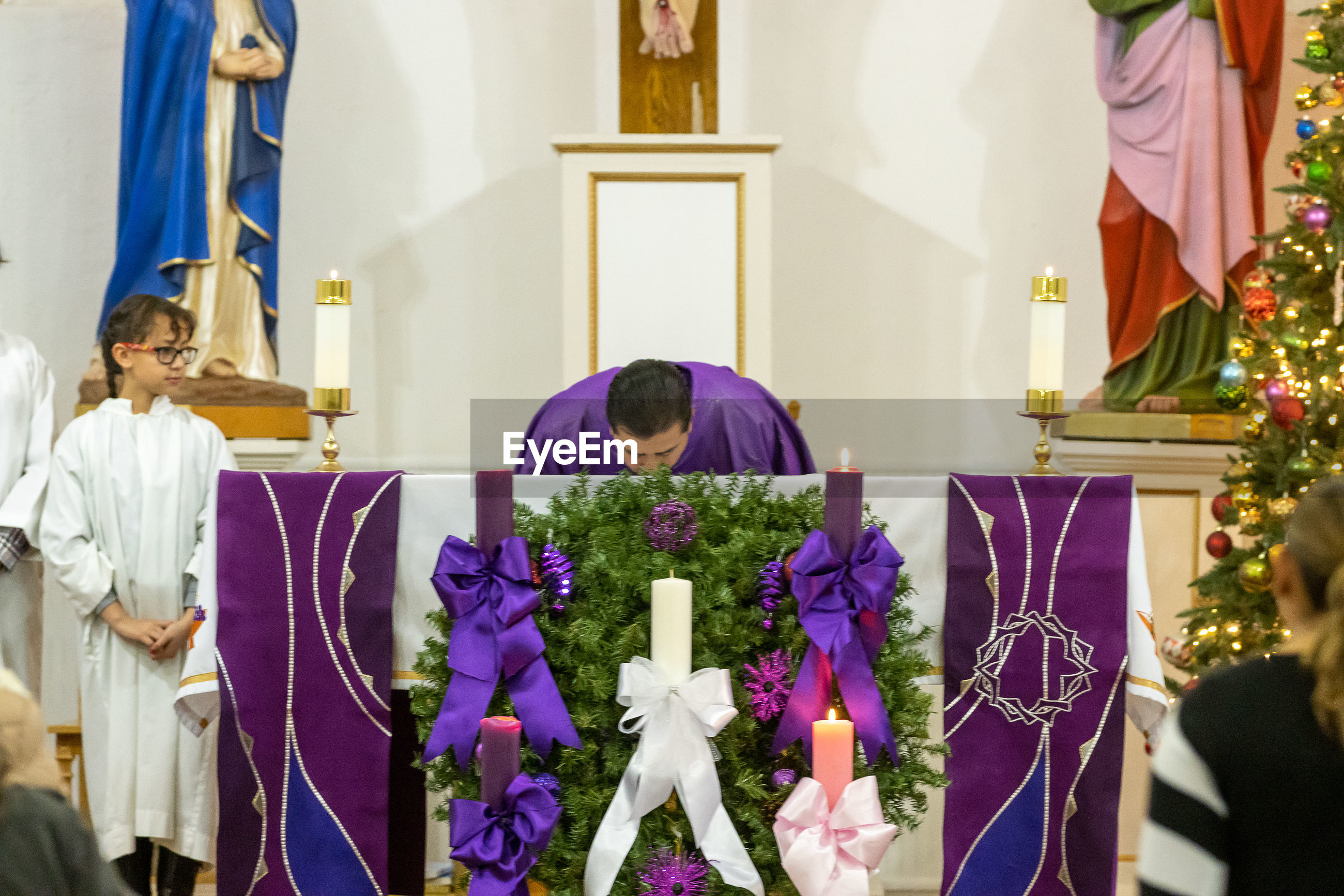 Priest kissing on table in church