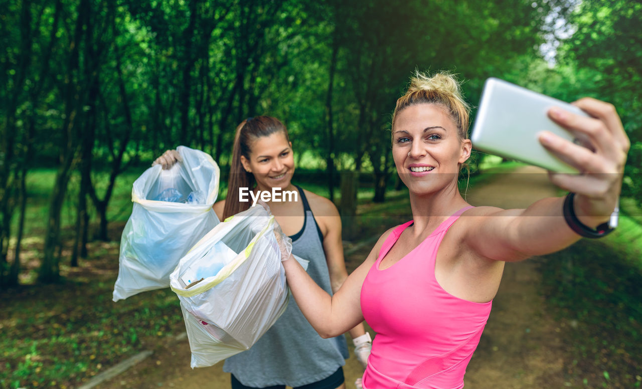 Female Friends Taking Selfie While Holding Garbage In Plastic Bags At Park