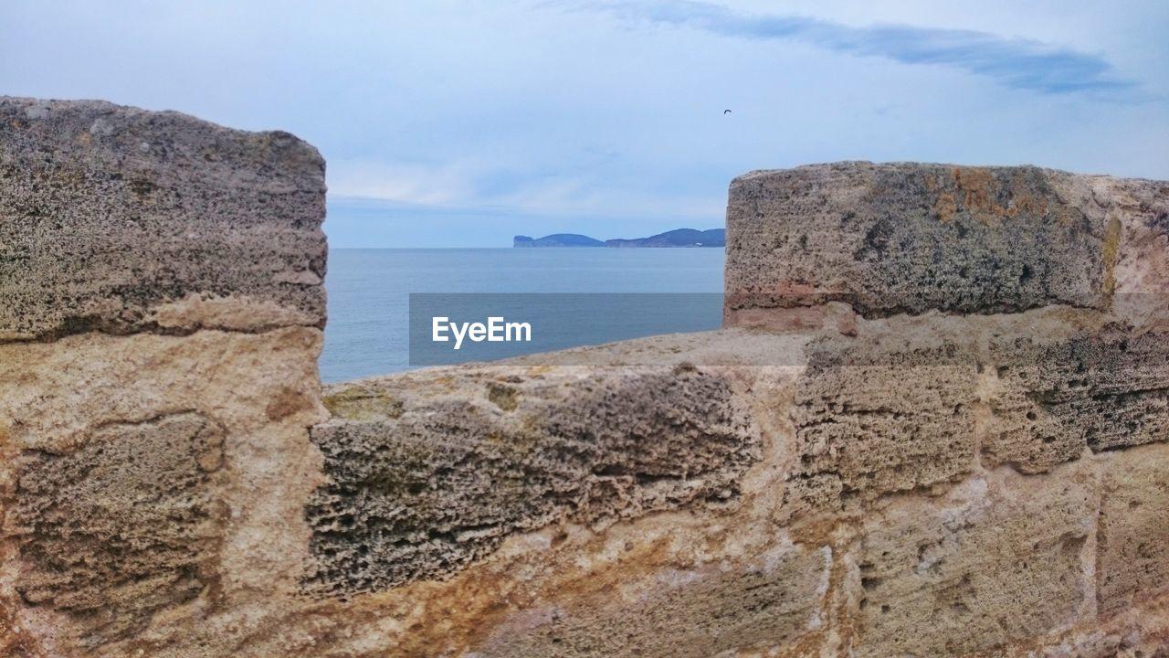 Sea seen through surrounding wall against sky