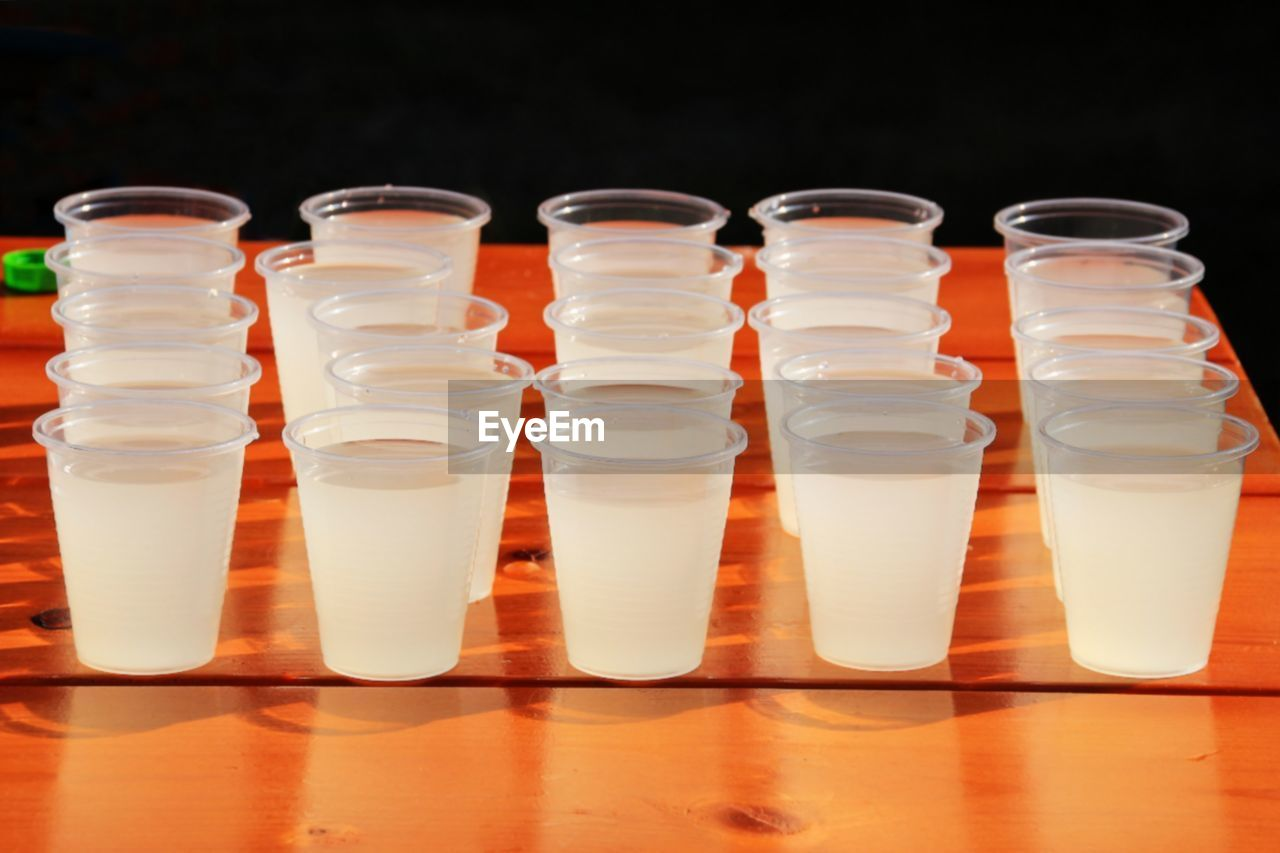 in a row, indoors, no people, food and drink, container, glass - material, studio shot, black background, bottle, side by side, glass, still life, group of objects, healthy eating, order, reflection, food, choice, science