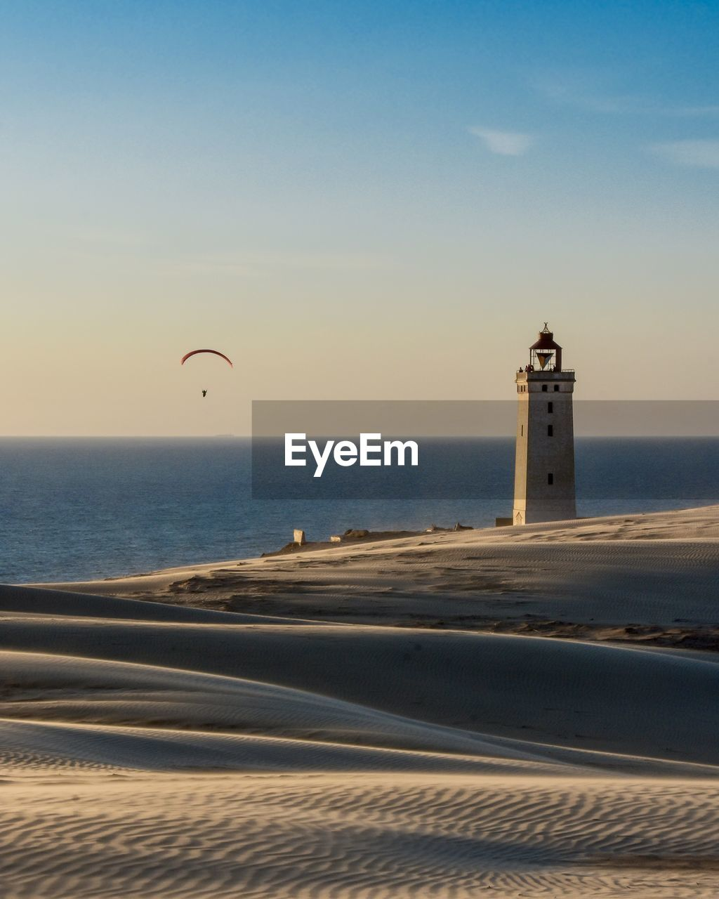 sea, sky, water, horizon, horizon over water, beach, land, scenics - nature, beauty in nature, nature, tower, sunset, built structure, sand, parachute, lighthouse, travel, tourism, architecture, outdoors