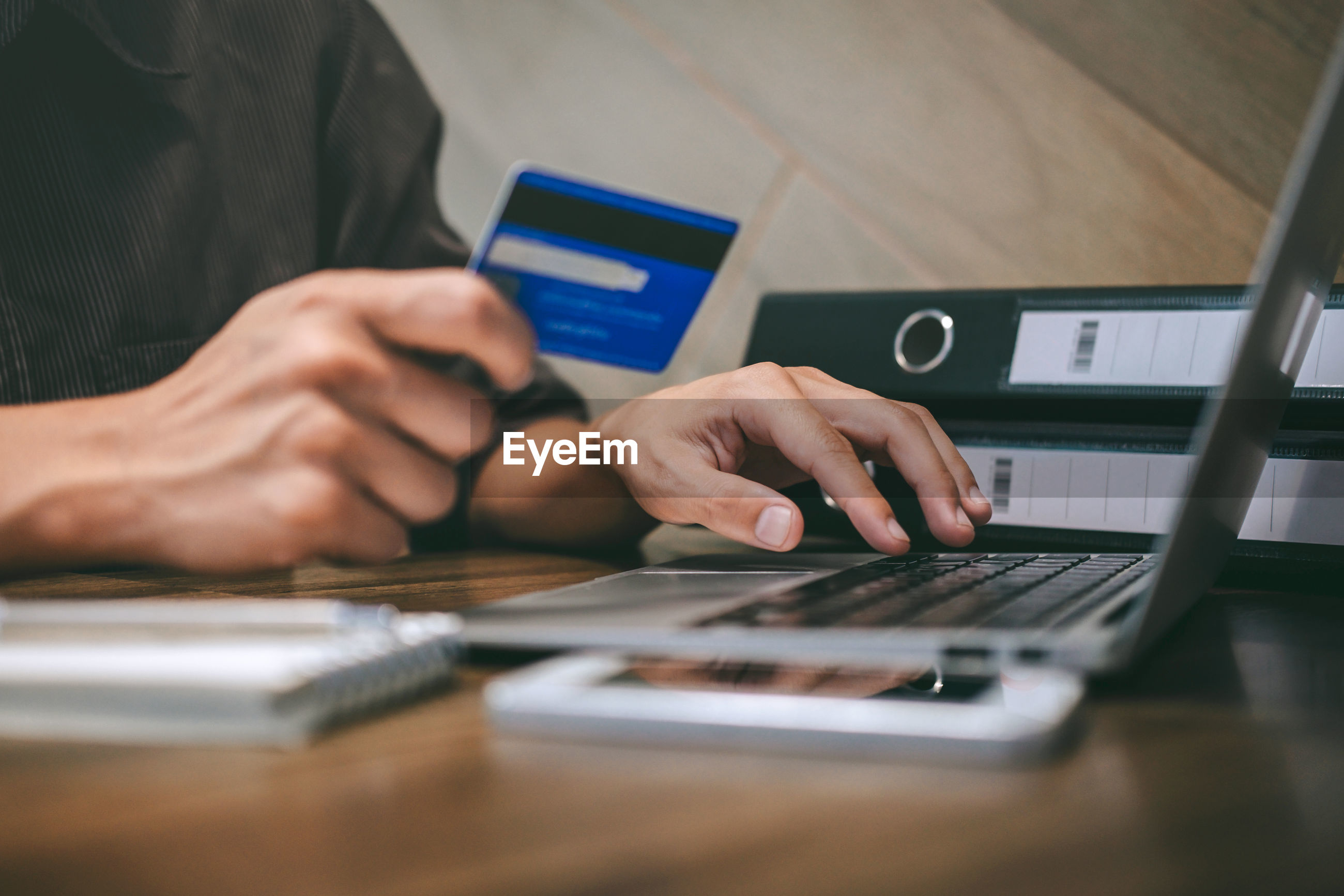 Midsection of businessman using laptop while holding credit card at desk in office