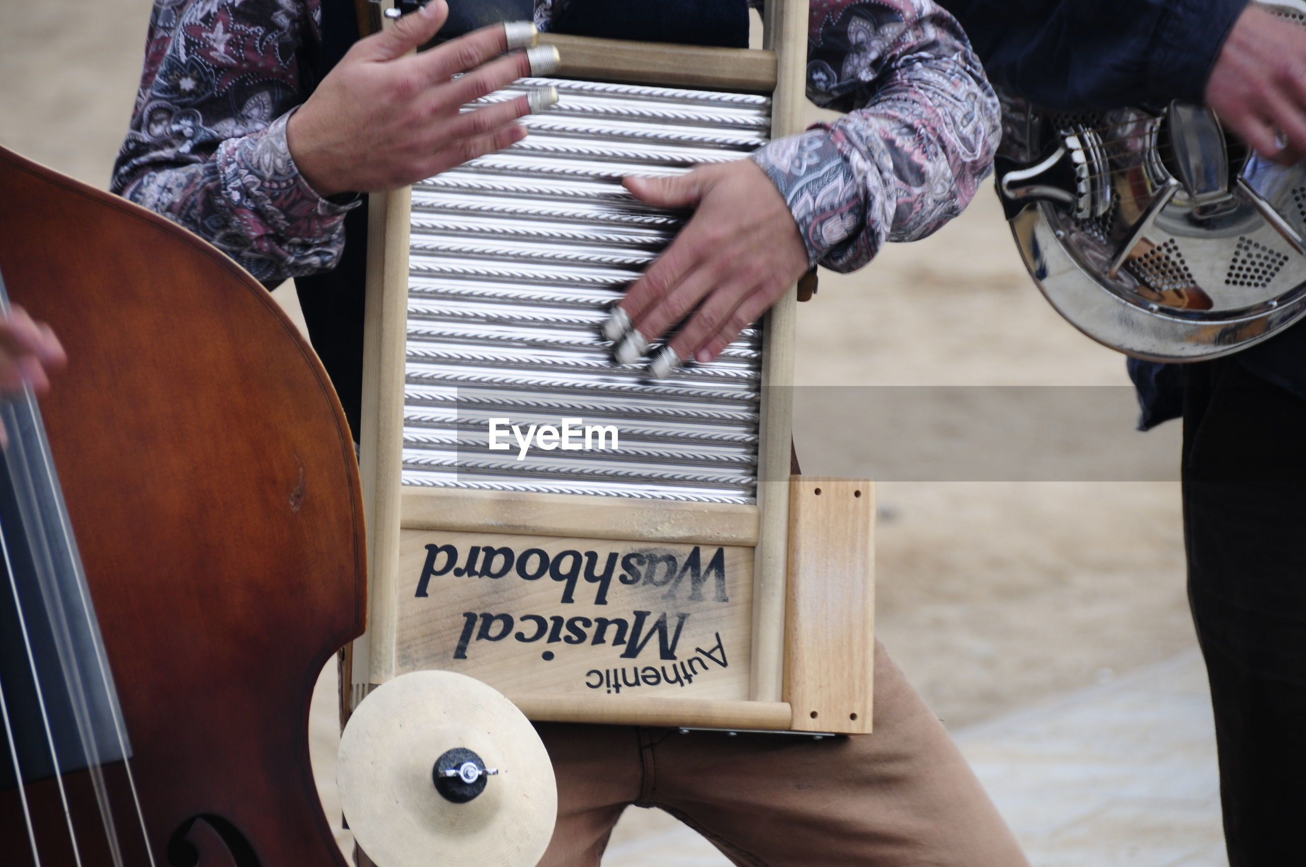 Midsection of man playing musical instrument outdoors