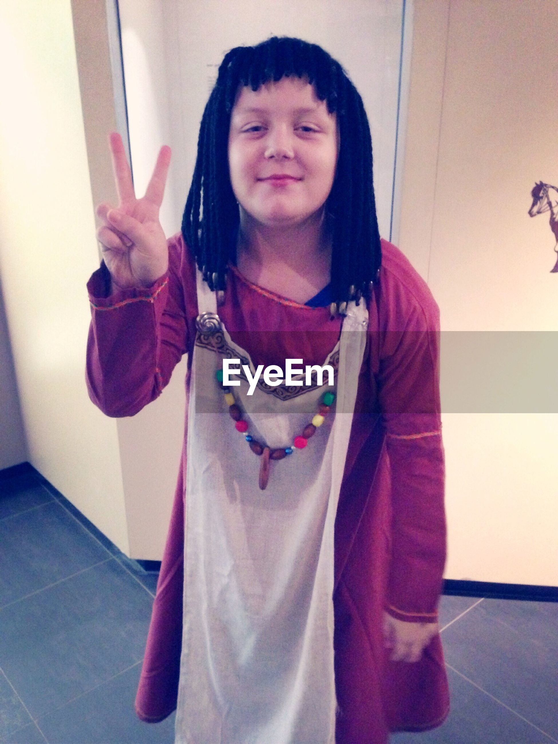 Portrait of boy in traditional cloths gesturing peace sign at home