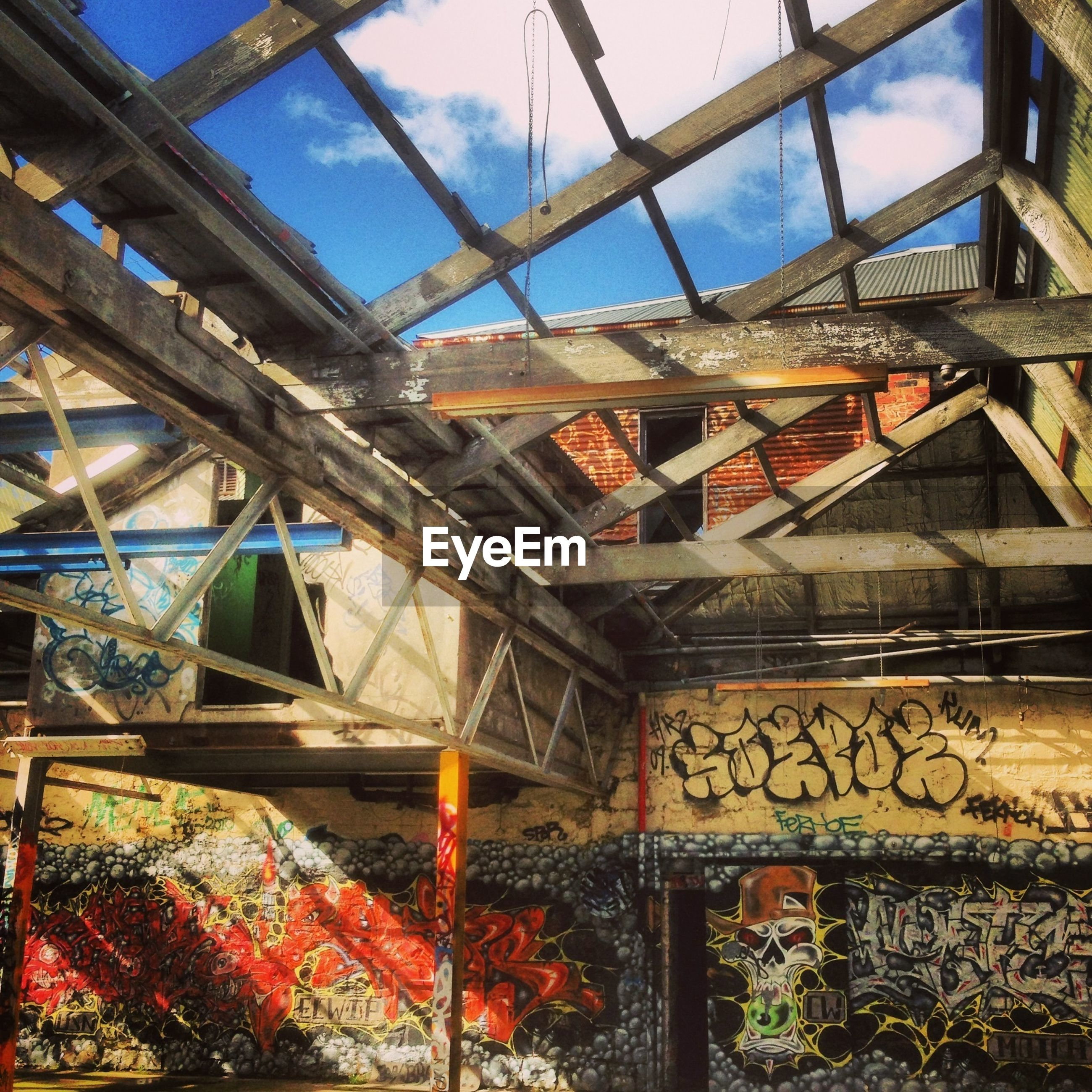built structure, architecture, low angle view, metal, building exterior, railing, sky, bridge - man made structure, metallic, day, graffiti, no people, sunlight, connection, outdoors, red, blue, house, wall - building feature, building