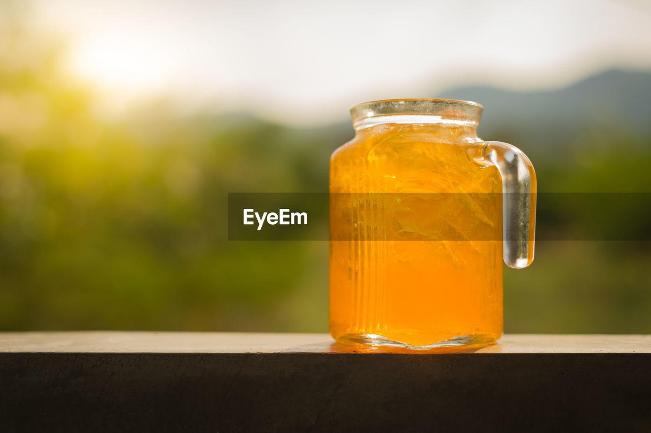 Close-Up Of Orange Juice In Glass Jar On Railing