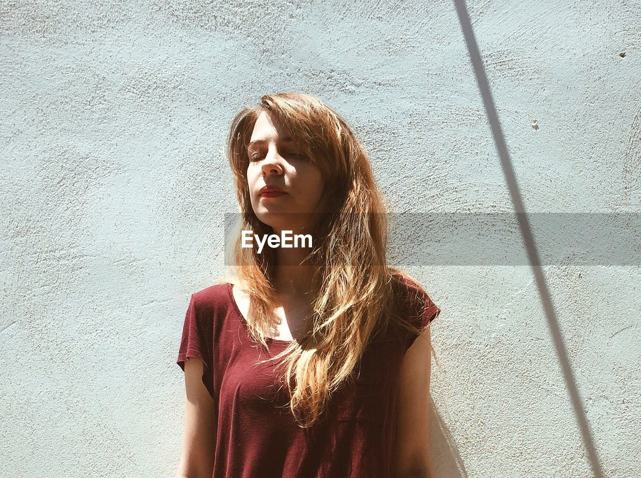 Low Angle View Of Woman With Eyes Closed Standing Against Wall