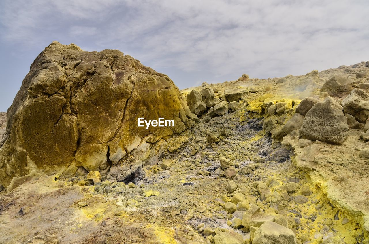 rock, rock - object, solid, sky, rock formation, beauty in nature, geology, tranquility, cloud - sky, nature, scenics - nature, physical geography, tranquil scene, no people, mountain, non-urban scene, day, rough, yellow, low angle view, eroded, formation, arid climate