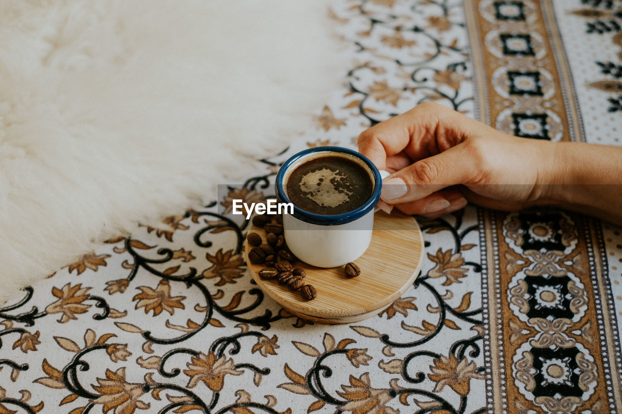 Cropped hand having coffee