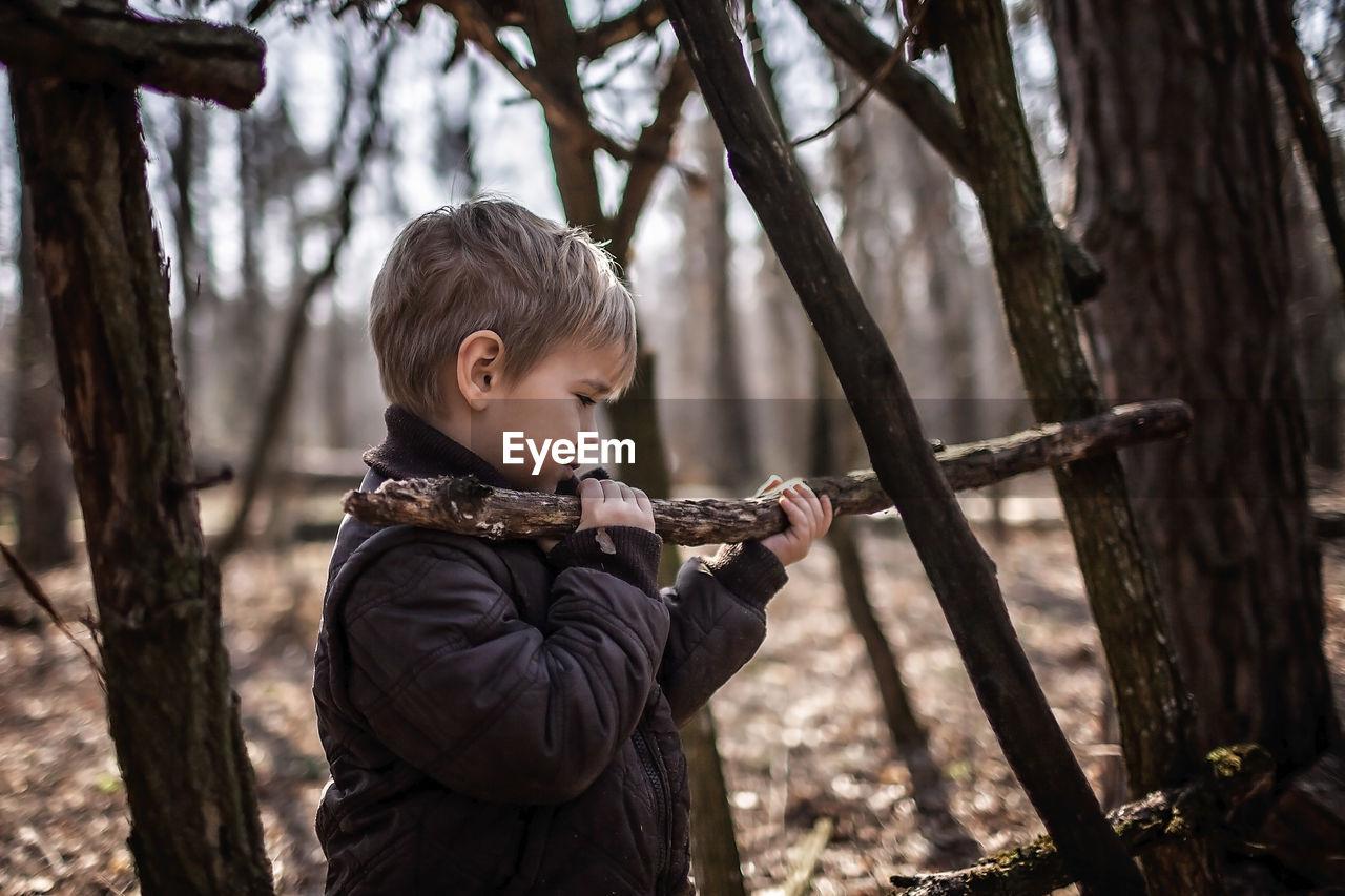FULL LENGTH OF BOY HOLDING TREE TRUNK