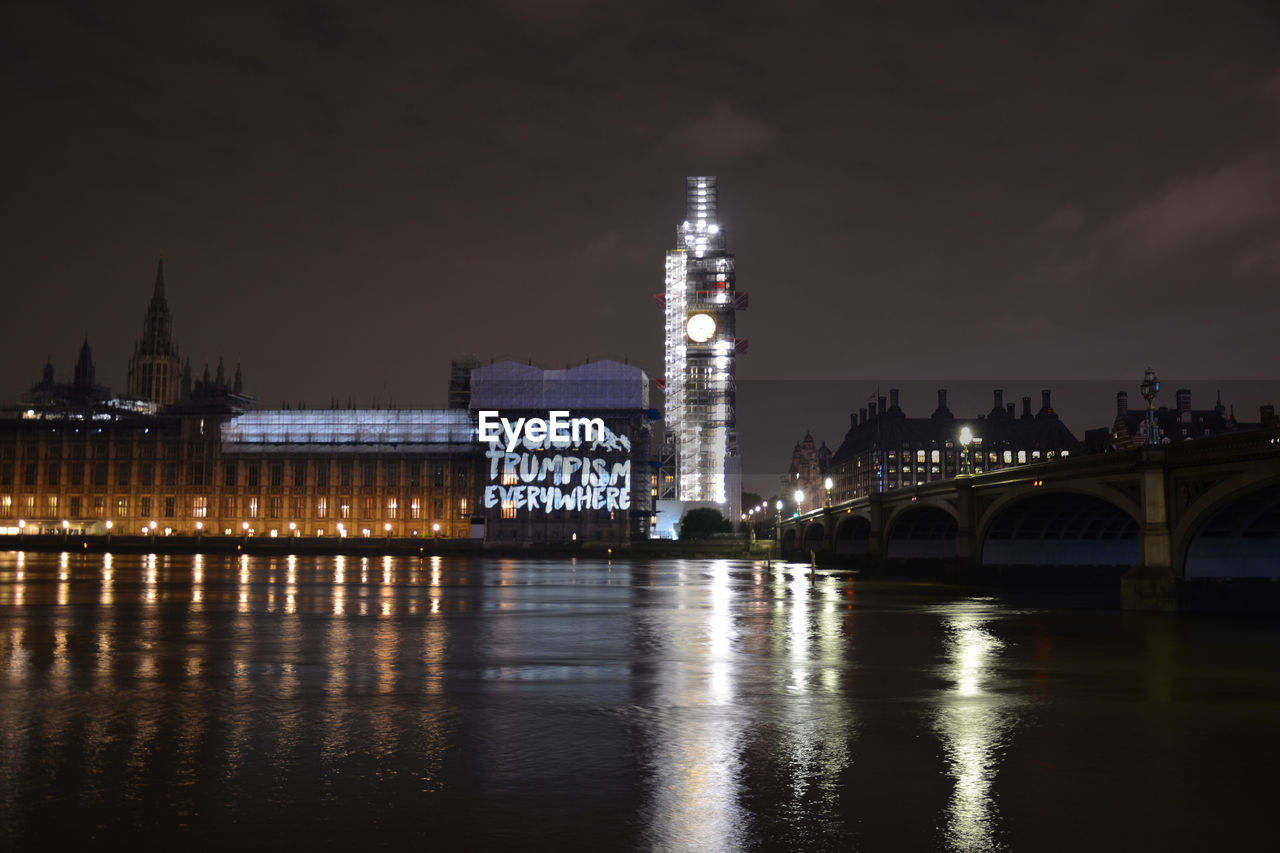 Reflection of illuminated bell tower on thames river in city at night