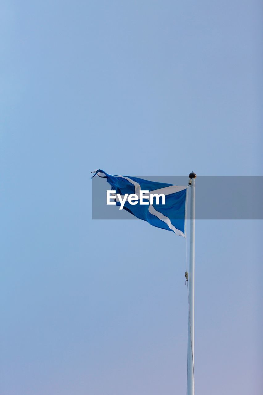 flag, patriotism, blue, sky, low angle view, wind, environment, copy space, clear sky, pole, no people, waving, day, nature, outdoors, motion, independence, striped, white color, national icon