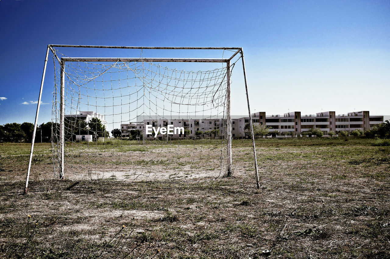 sport, soccer, soccer field, team sport, sky, soccer goal, sports equipment, football, goal post, net - sports equipment, grass, land, nature, field, playing field, goal, plant, clear sky, no people, day, outdoors