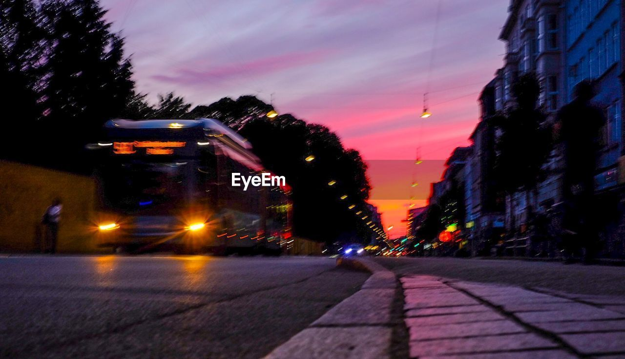 street, sky, city, illuminated, transportation, architecture, mode of transportation, built structure, building exterior, road, sunset, land vehicle, car, motor vehicle, nature, cloud - sky, the way forward, direction, motion, no people, outdoors, light