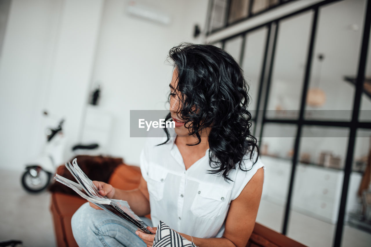 Woman reading book while sitting in office