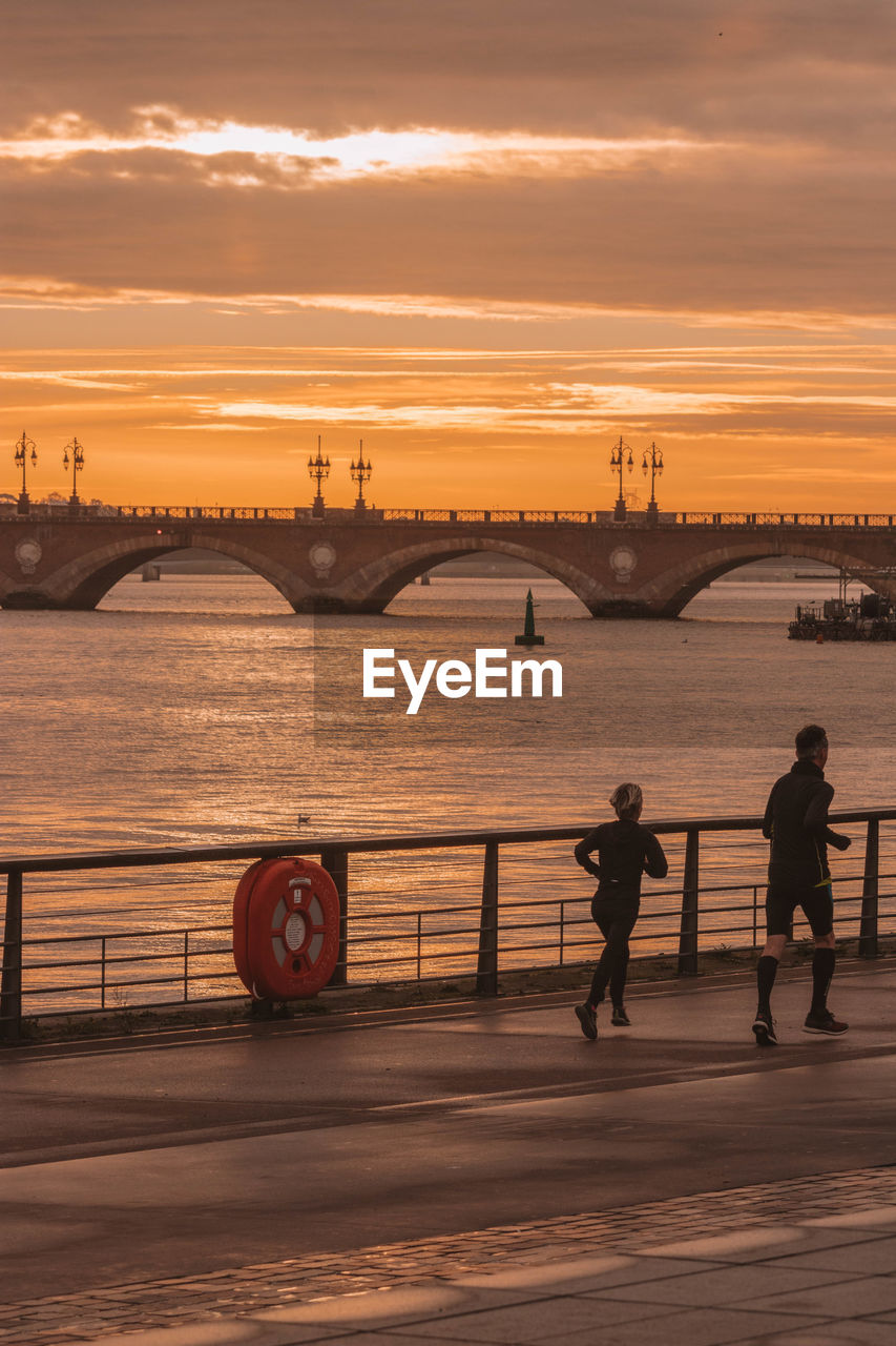 sunset, sky, water, bridge, built structure, architecture, bridge - man made structure, connection, cloud - sky, transportation, orange color, men, real people, nature, lifestyles, river, full length, group of people, outdoors