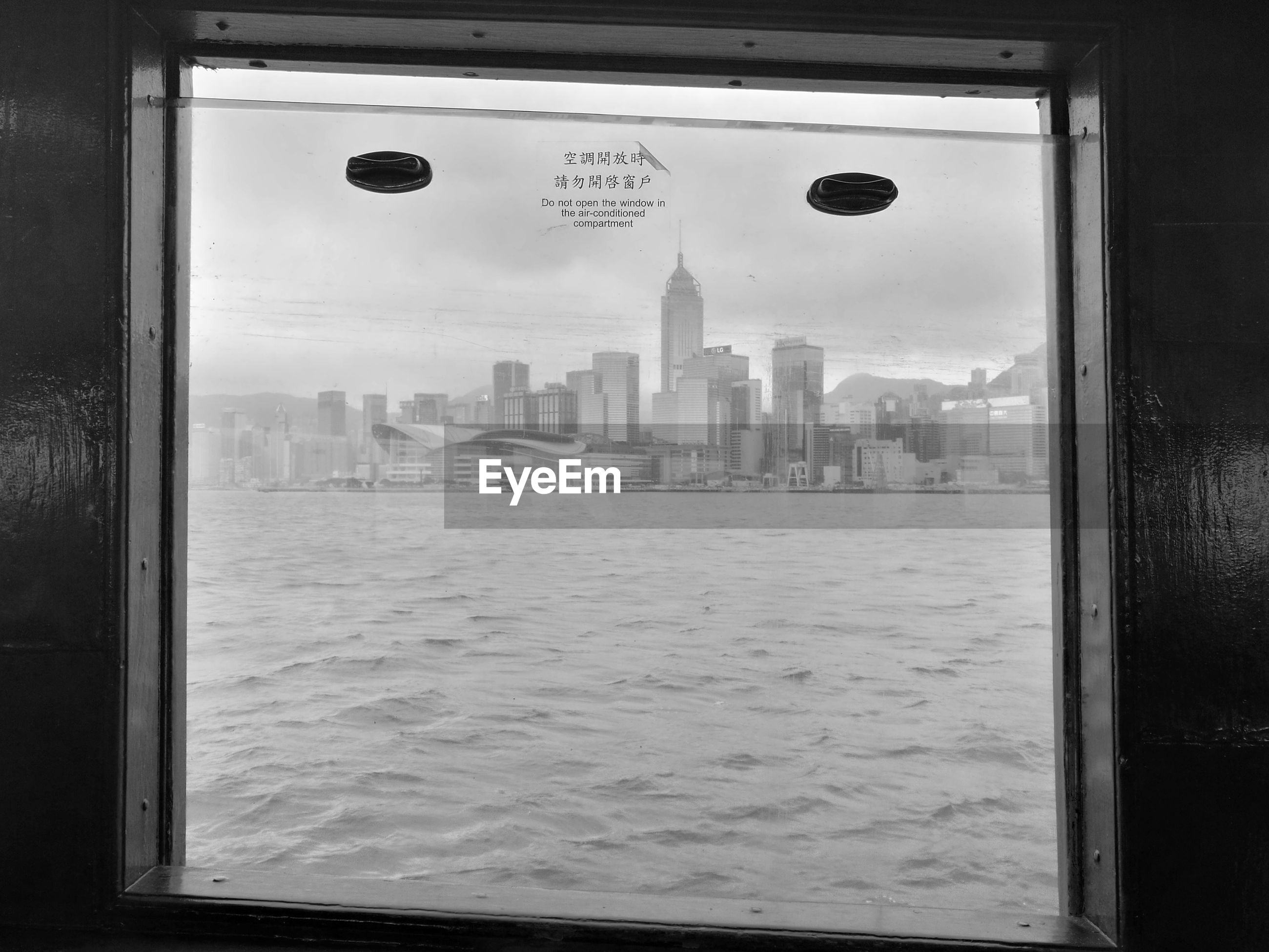 Cityscape by sea against sky seen through star ferry window