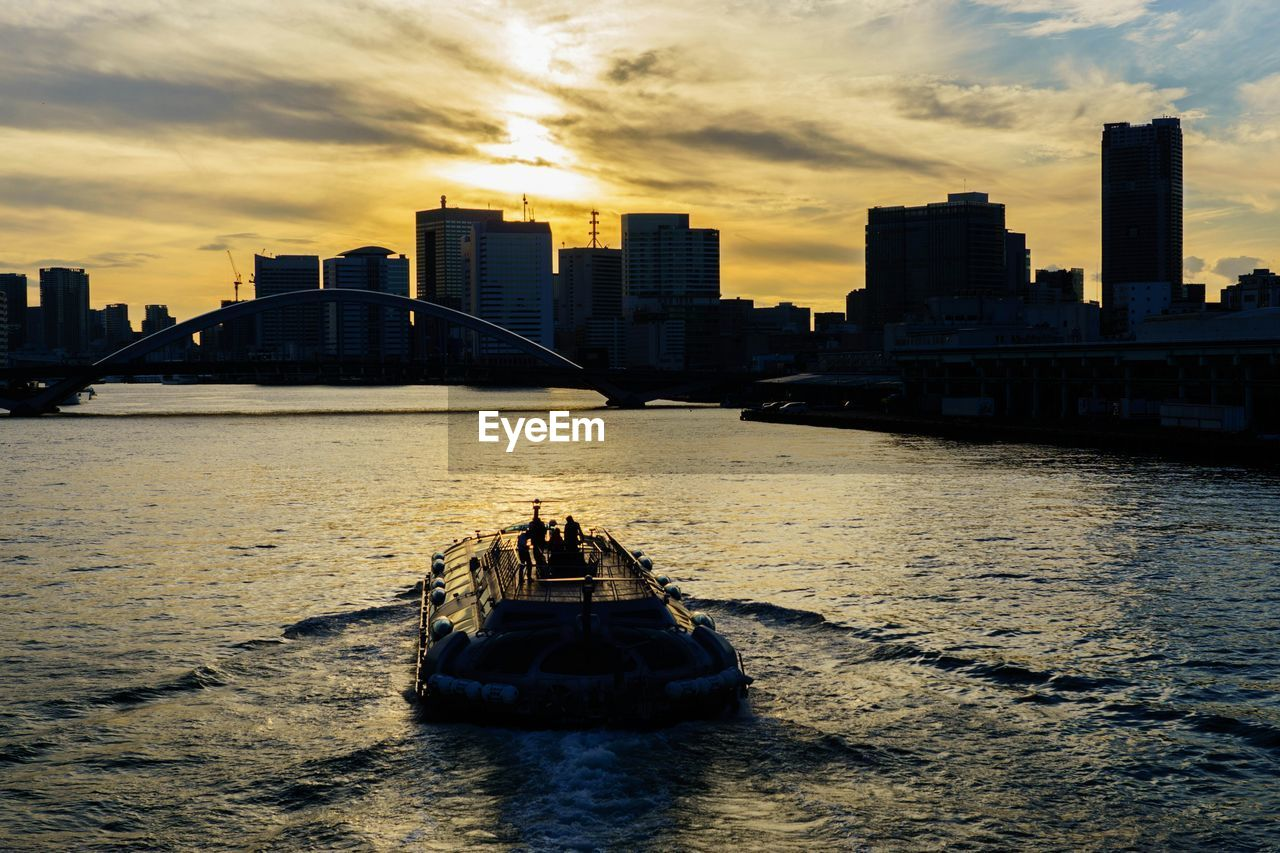 architecture, built structure, building exterior, city, sky, skyscraper, river, cloud - sky, water, sunset, bridge - man made structure, connection, transportation, waterfront, urban skyline, rippled, outdoors, nautical vessel, cityscape, travel destinations, no people, suspension bridge, modern, ferry, nature, day
