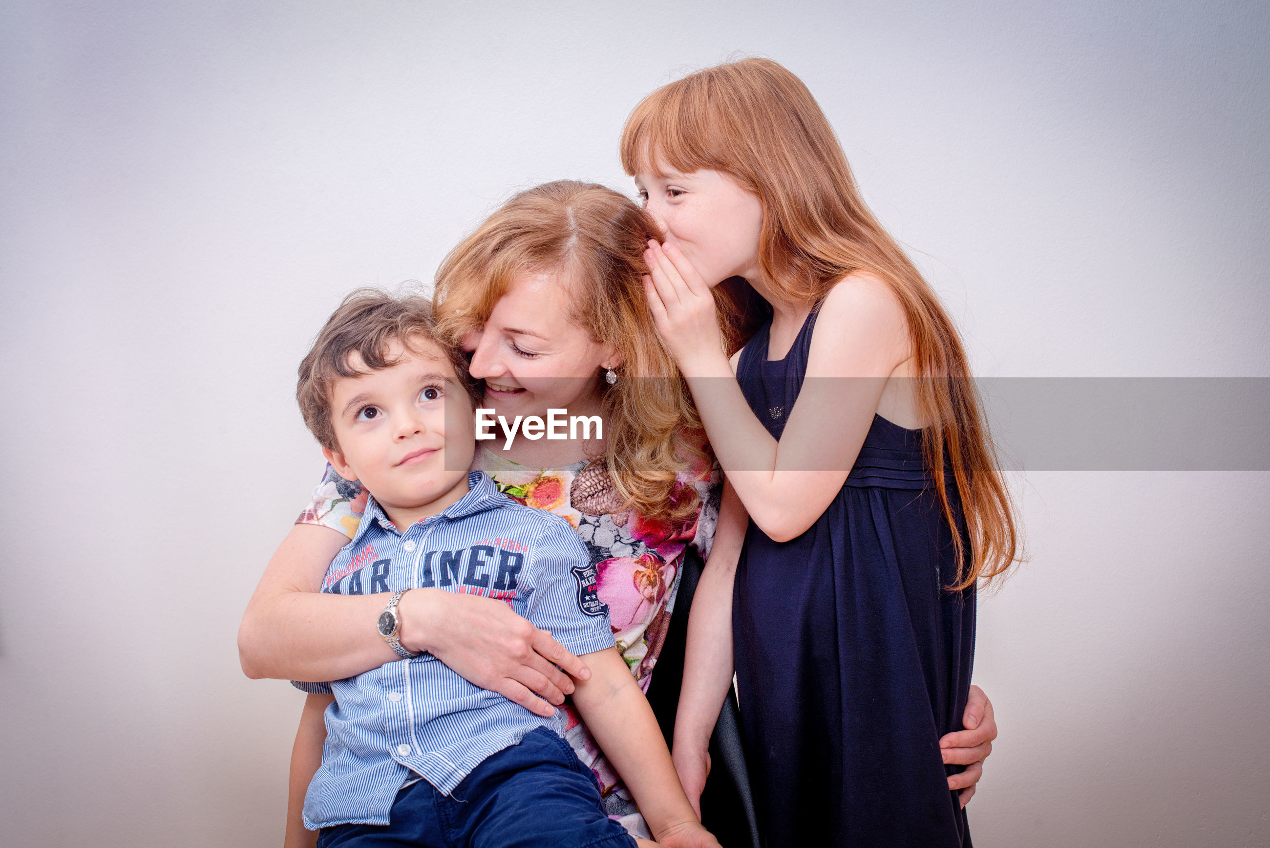Happy mother with children against white wall at home