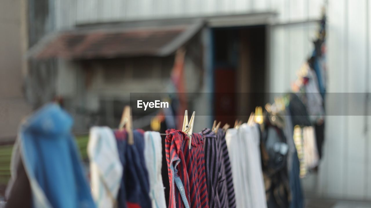 clothing, hanging, retail, focus on foreground, choice, built structure, multi colored, selective focus, for sale, coathanger, architecture, day, building exterior, variation, store, in a row, clothes rack, large group of objects, protection, side by side, retail display, sale, consumerism