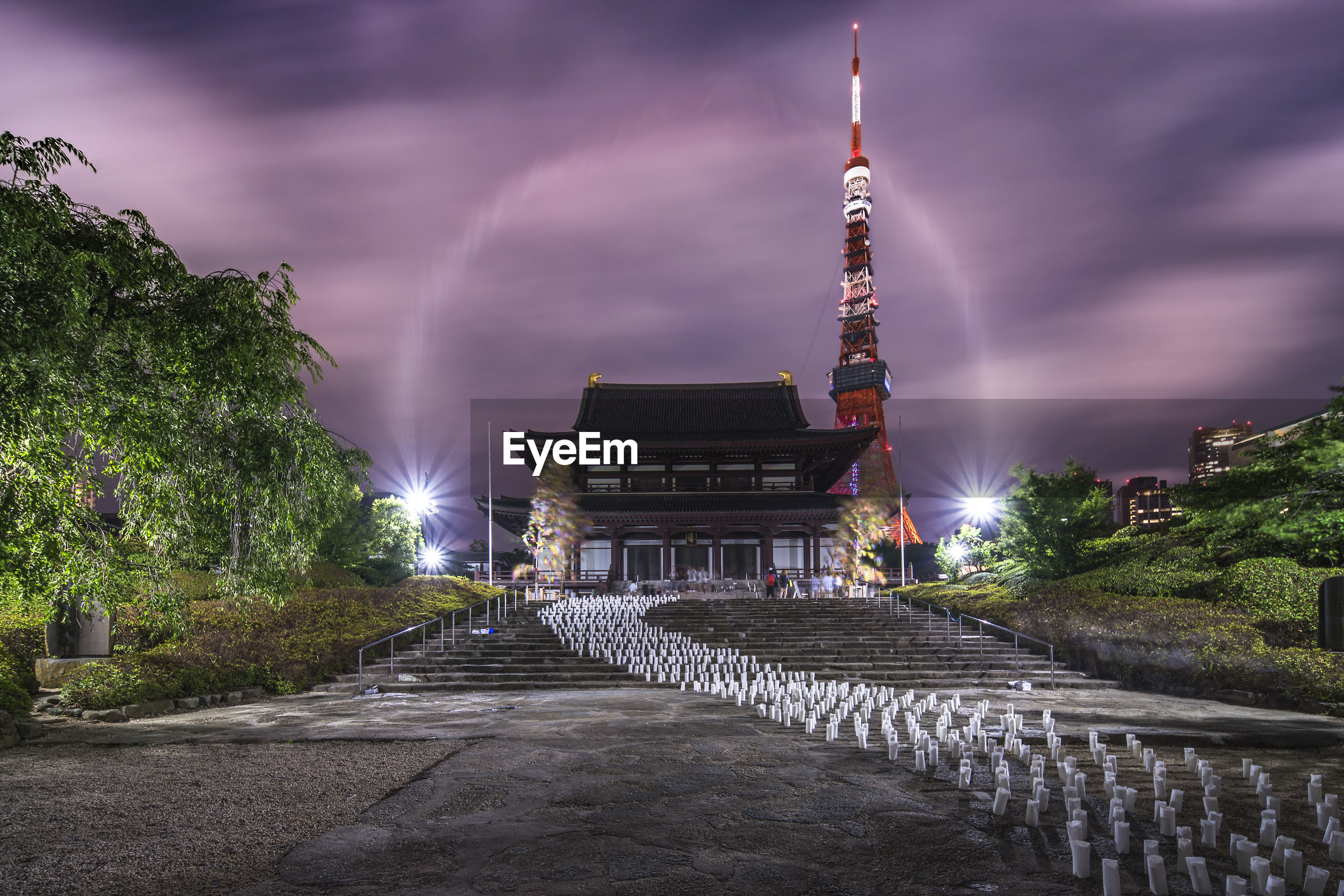 ILLUMINATED TEMPLE AMIDST BUILDINGS IN CITY