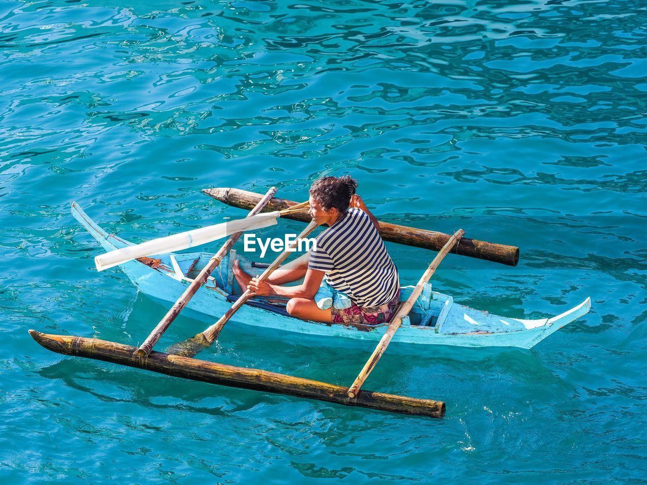oar, nautical vessel, transportation, water, real people, one person, mode of transport, leisure activity, day, high angle view, rowing, rear view, men, wooden raft, outdoors, raft, nature, sailing, beauty in nature, gondola - traditional boat, people