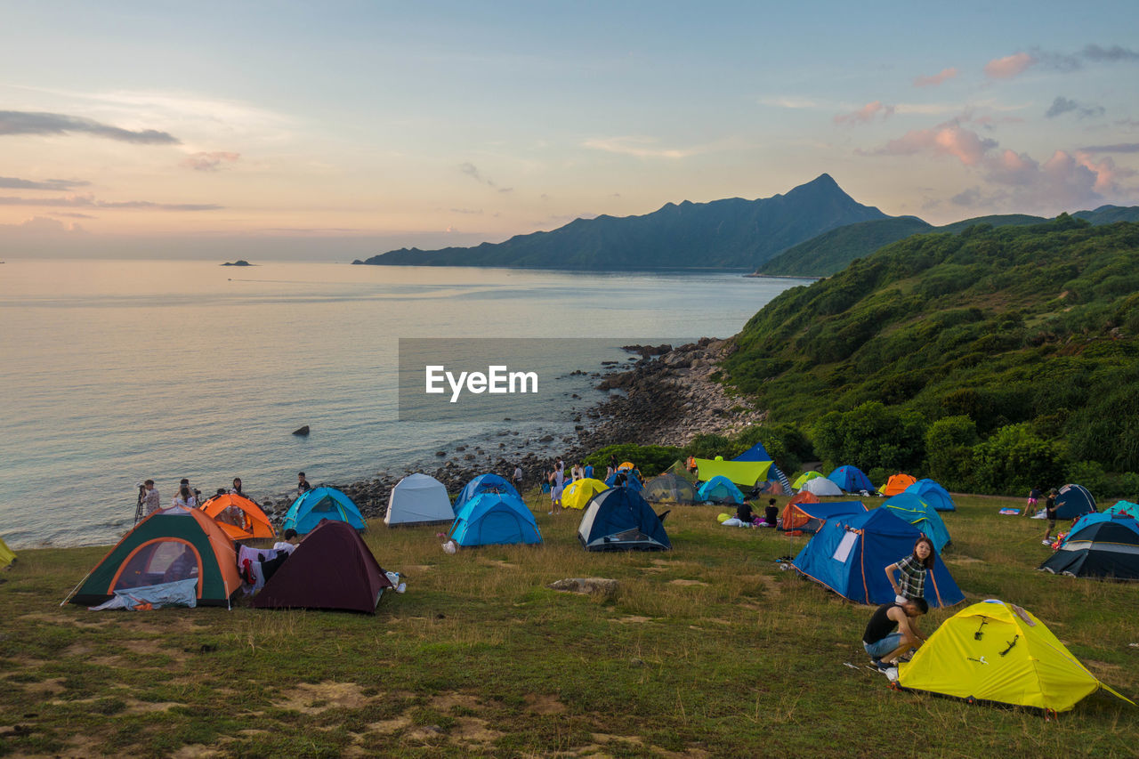 tent, camping, sea, beach, nature, beauty in nature, water, sky, shelter, real people, vacations, scenics, sunset, tranquil scene, tranquility, mountain, adventure, sand, outdoors, day, men, horizon over water, women, grass, people