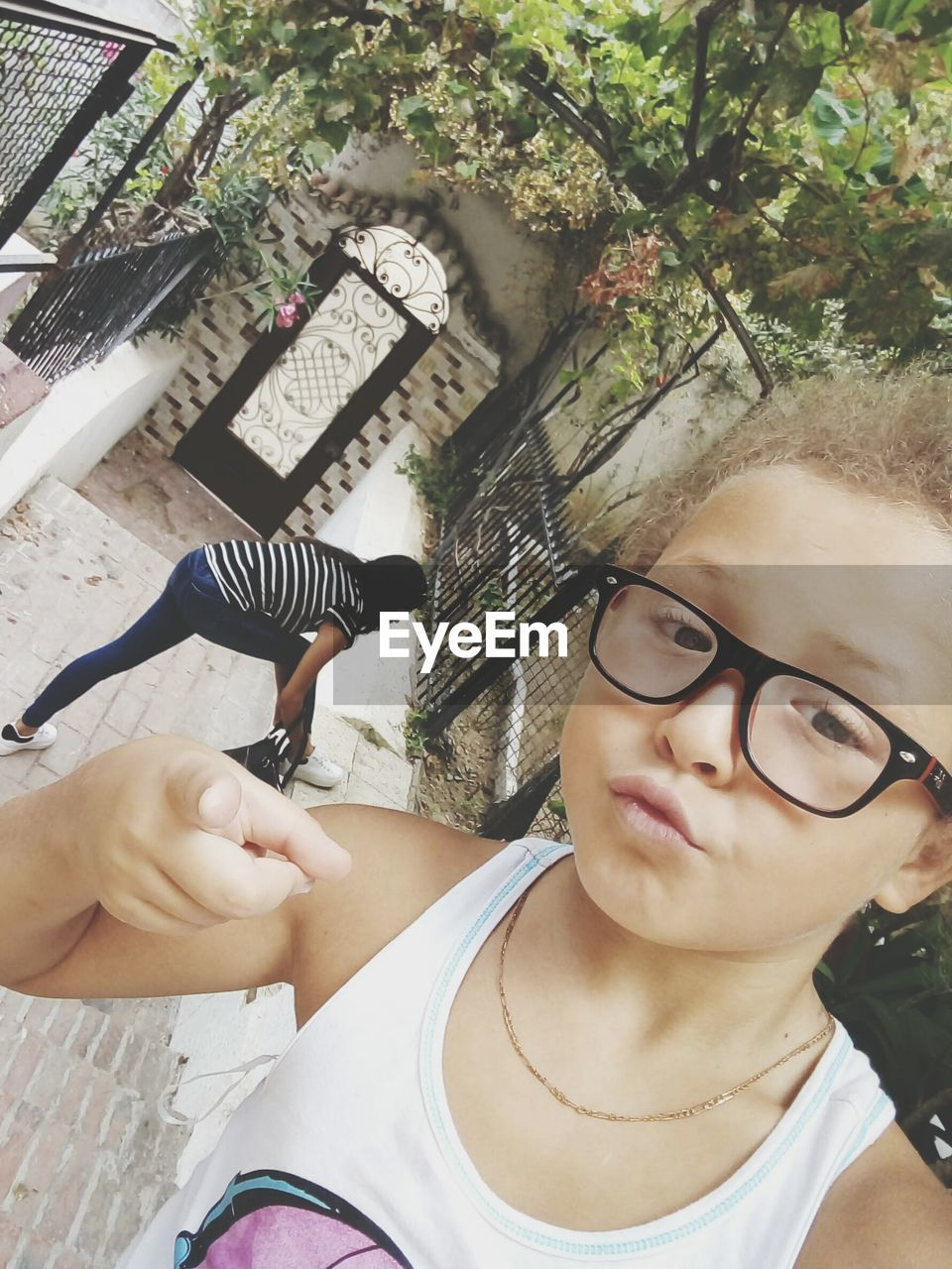 real people, eyeglasses, one person, young adult, young women, front view, lifestyles, day, tree, leisure activity, glasses, human face, outdoors, close-up, human hand, mammal