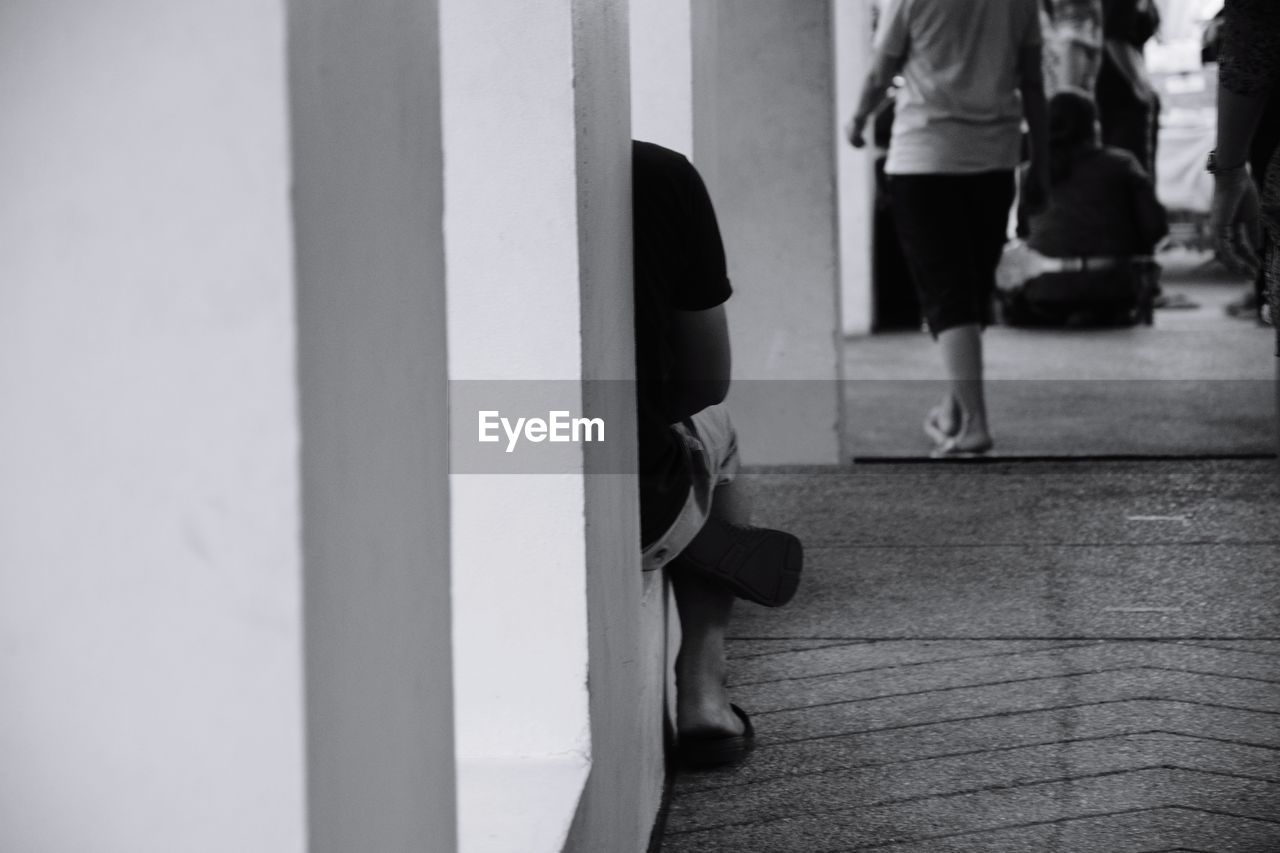 Cropped image of person sitting by wall in corridor