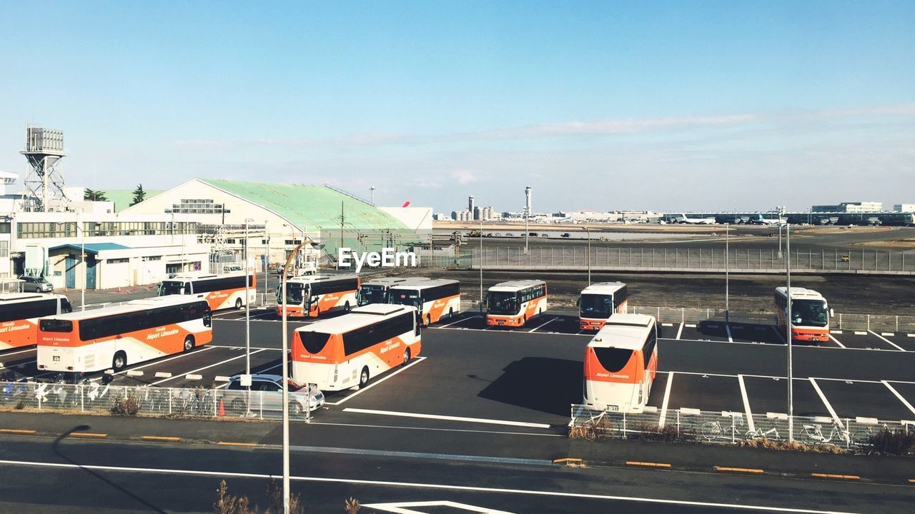 Buses Parked At Parking Lot Against Sky