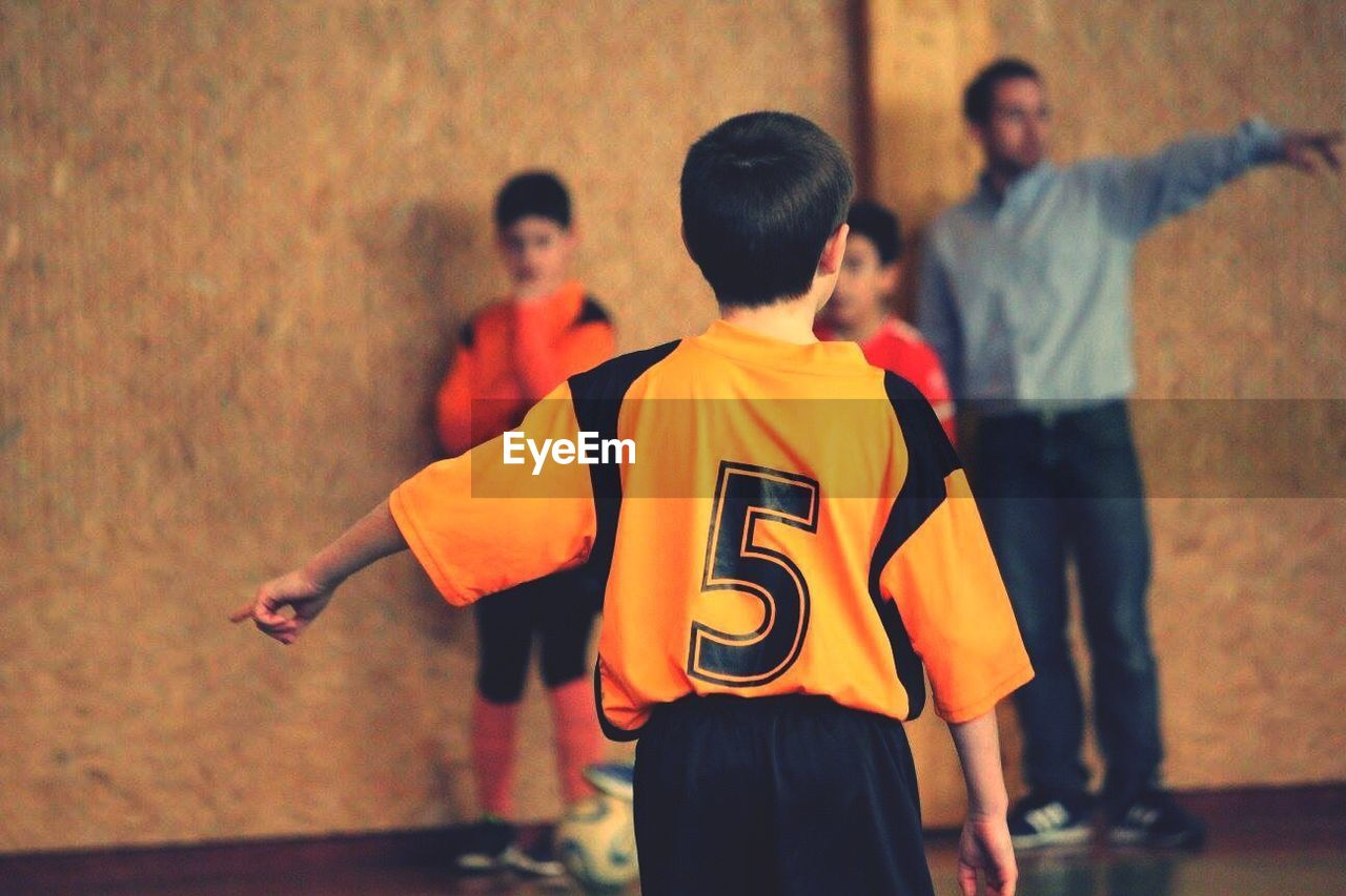 Rear view of boy pointing while playing soccer