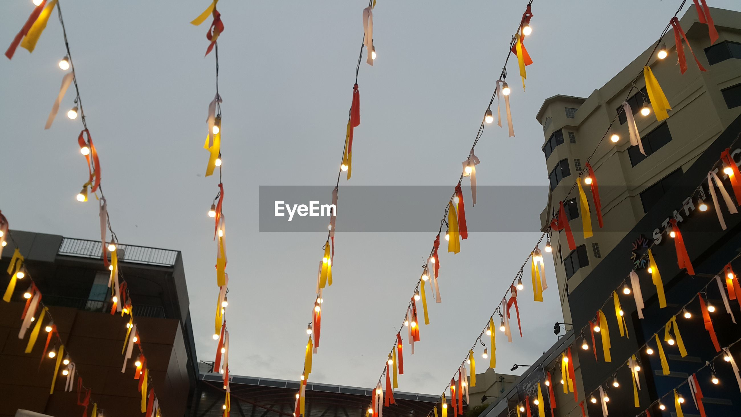 Low angle view of illuminated lights against building and sky at night