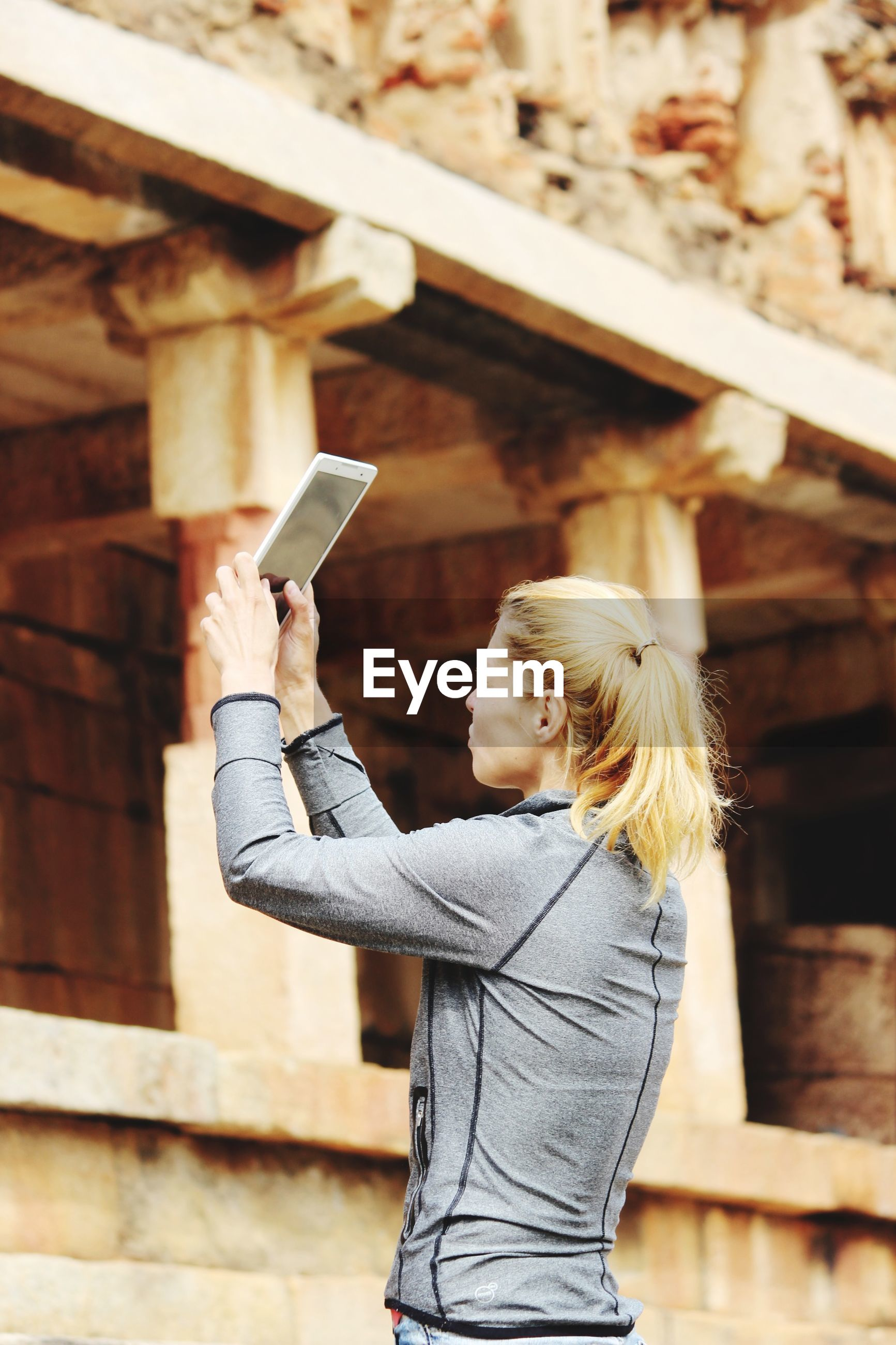 Woman photographing through digital tablet at old ruins