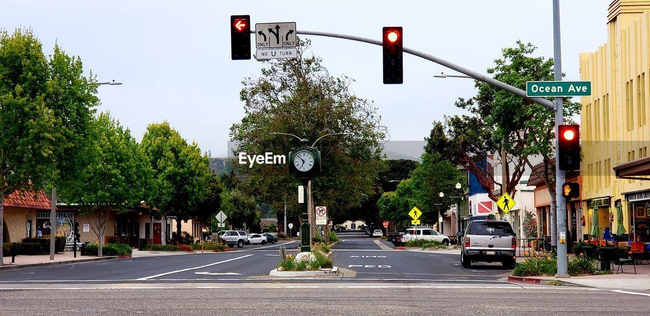 Illuminated stoplight on road against trees