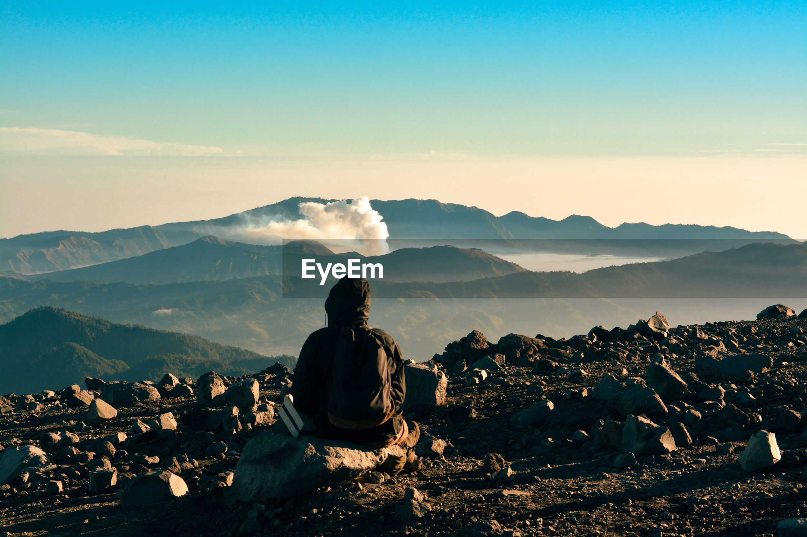 Rear view of person sitting on rock against mountain and sky