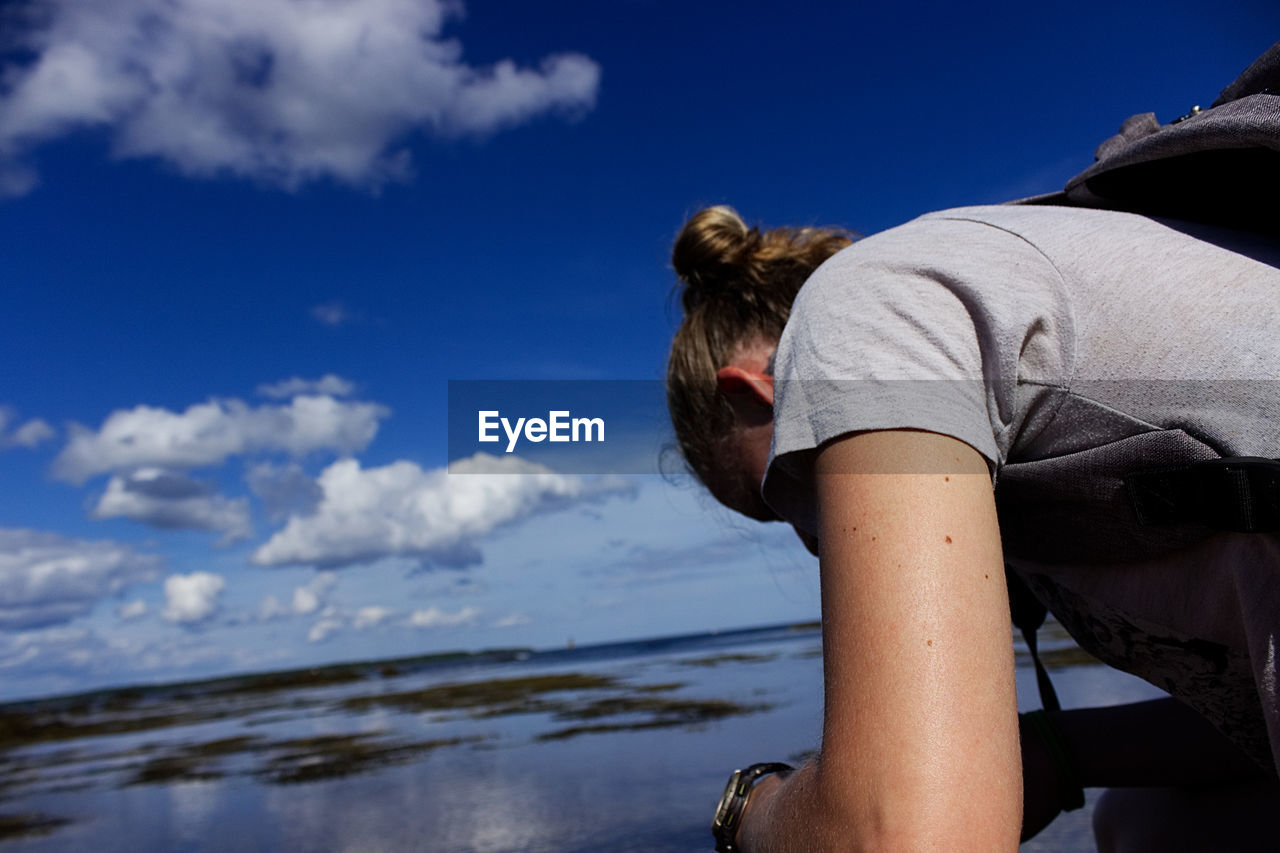Low Angle View Of Woman By Lake Against Blue Sky