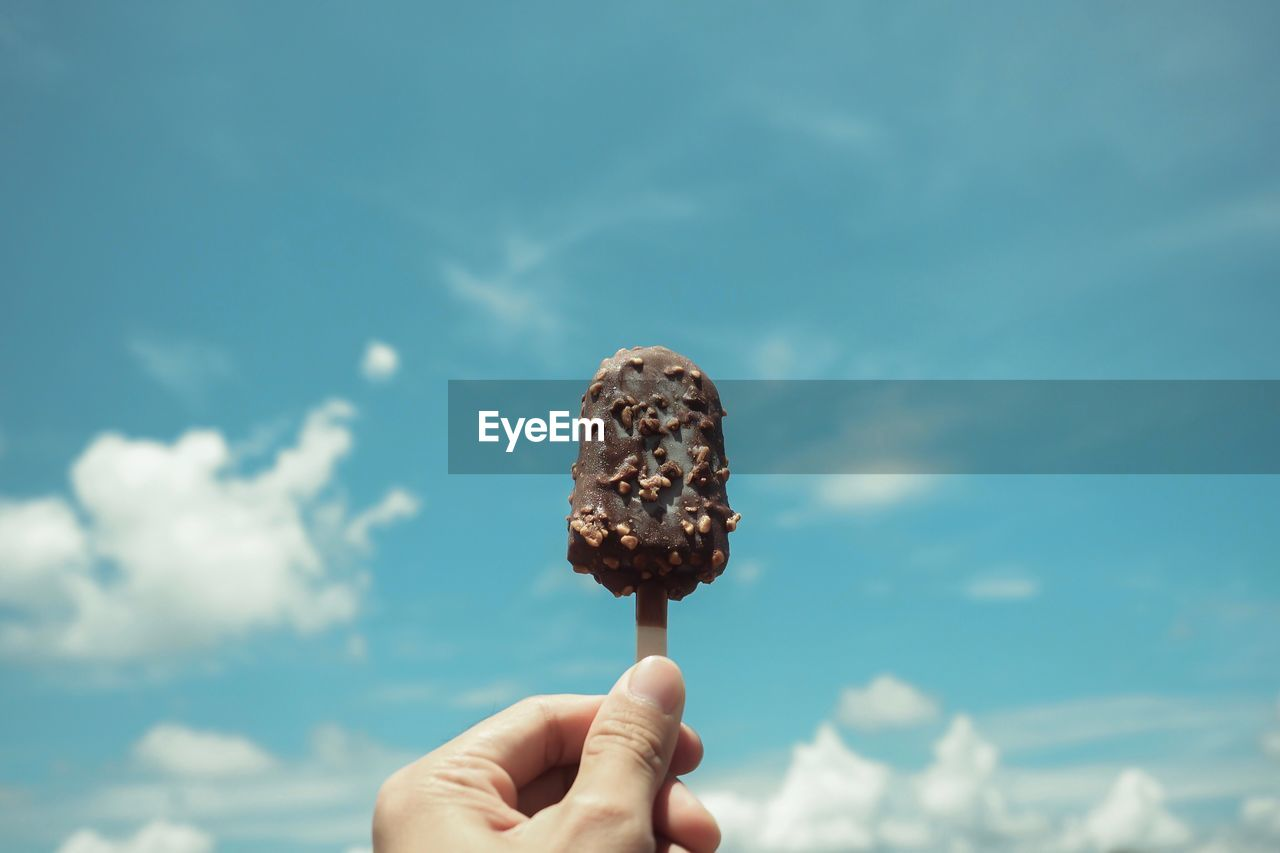 Cropped image of hand holding chocolate ice cream bar against blue sky