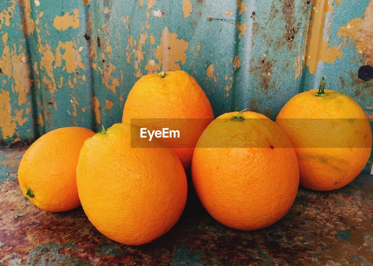 Close-Up Of Oranges Against Rusty Metal