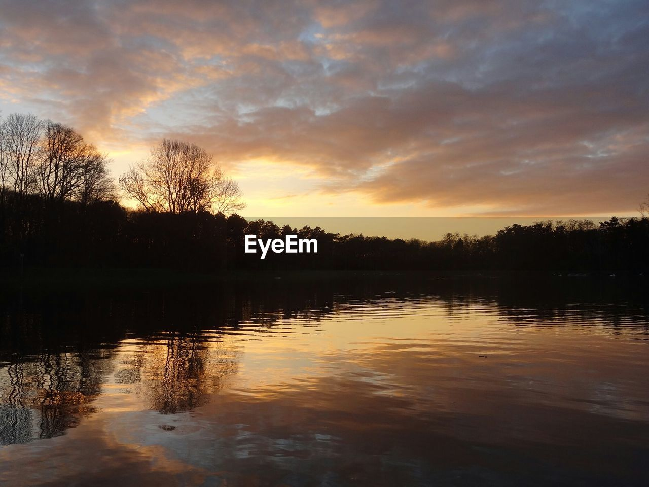 Idyllic view of calm lake against sky during sunset