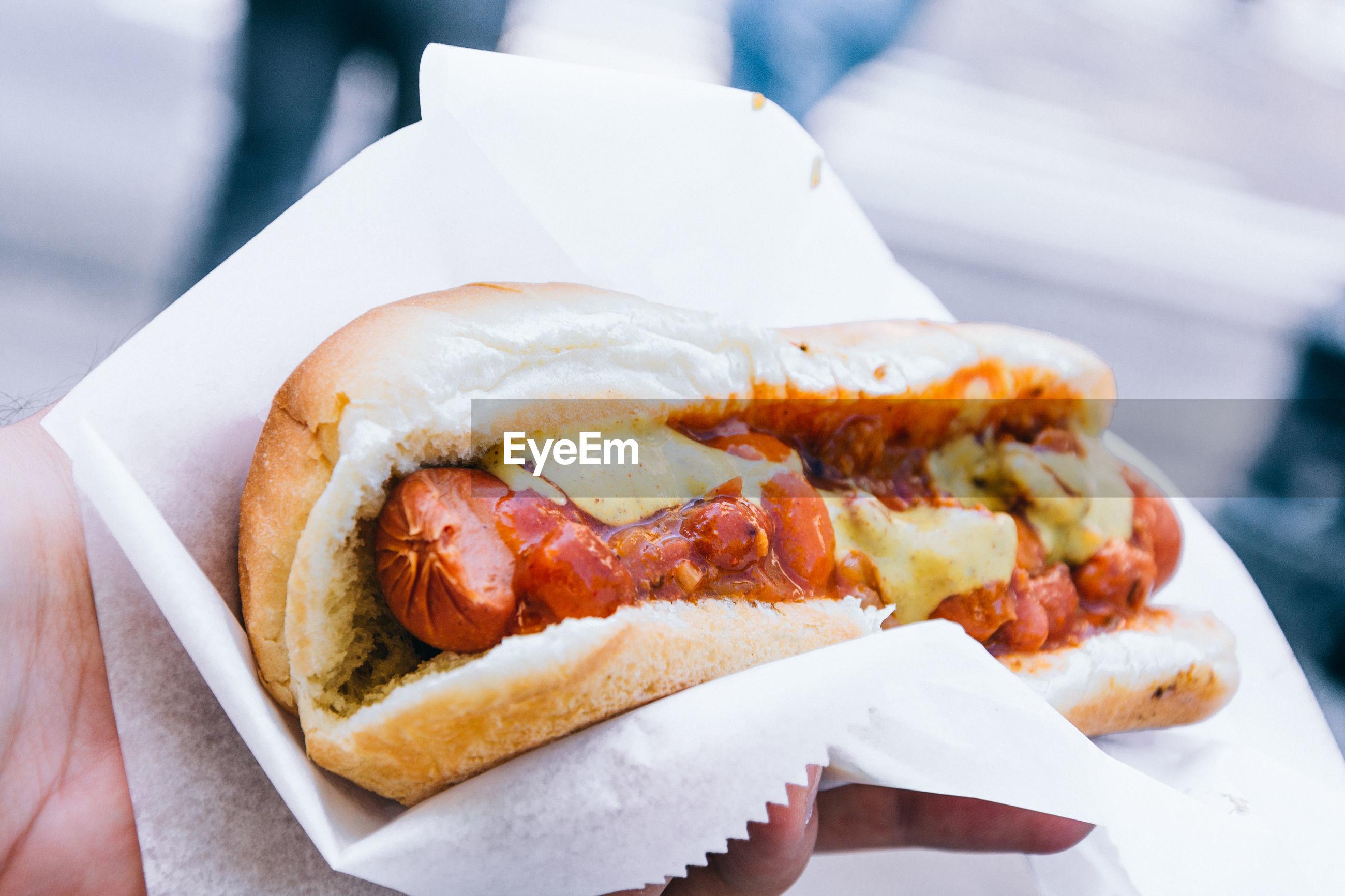 Cropped image of hand holding hot dog