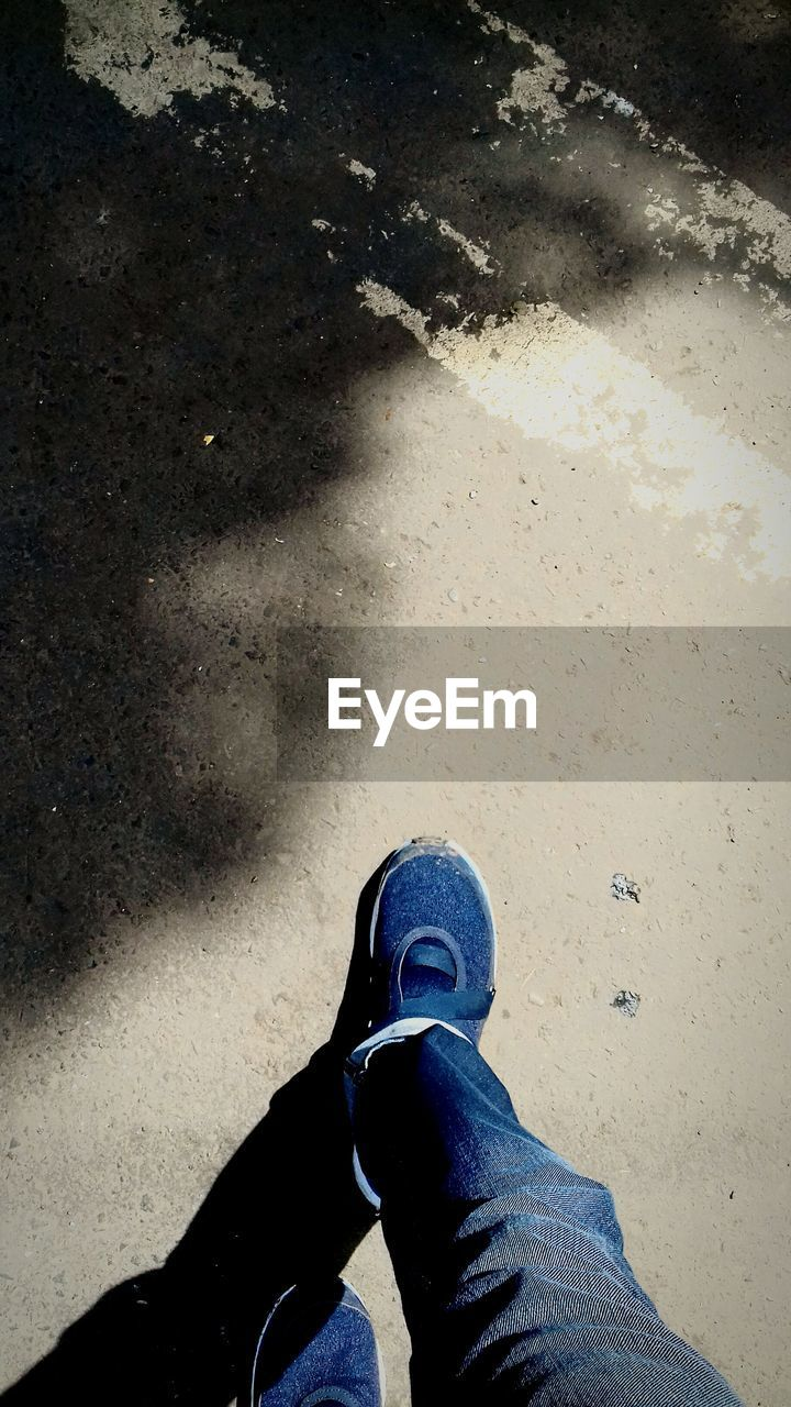 low section, human leg, shoe, real people, personal perspective, one person, standing, high angle view, jeans, day, outdoors, human body part, men, close-up, human, people