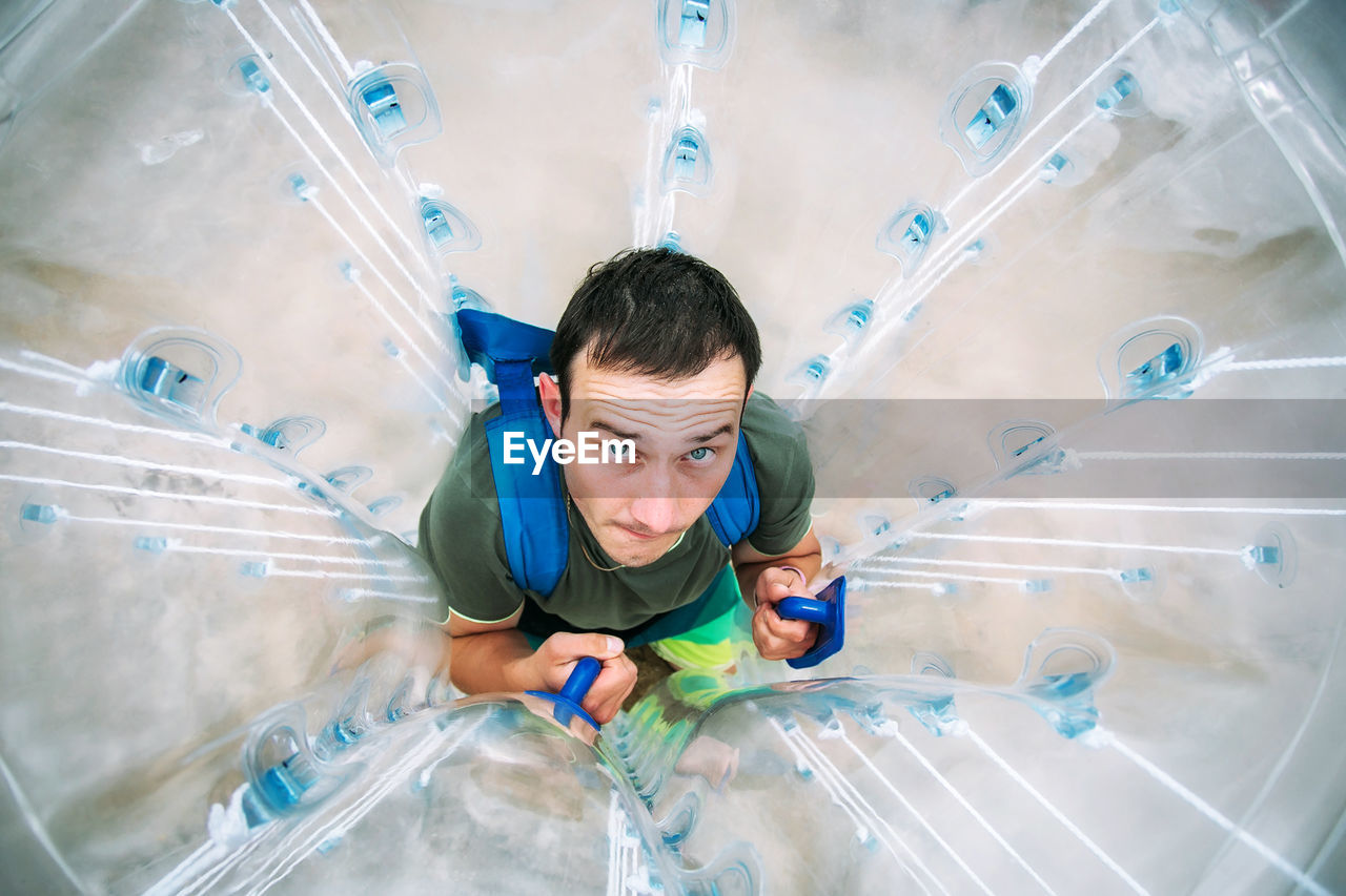 High Angle View Portrait Of Man In Zorb Ball