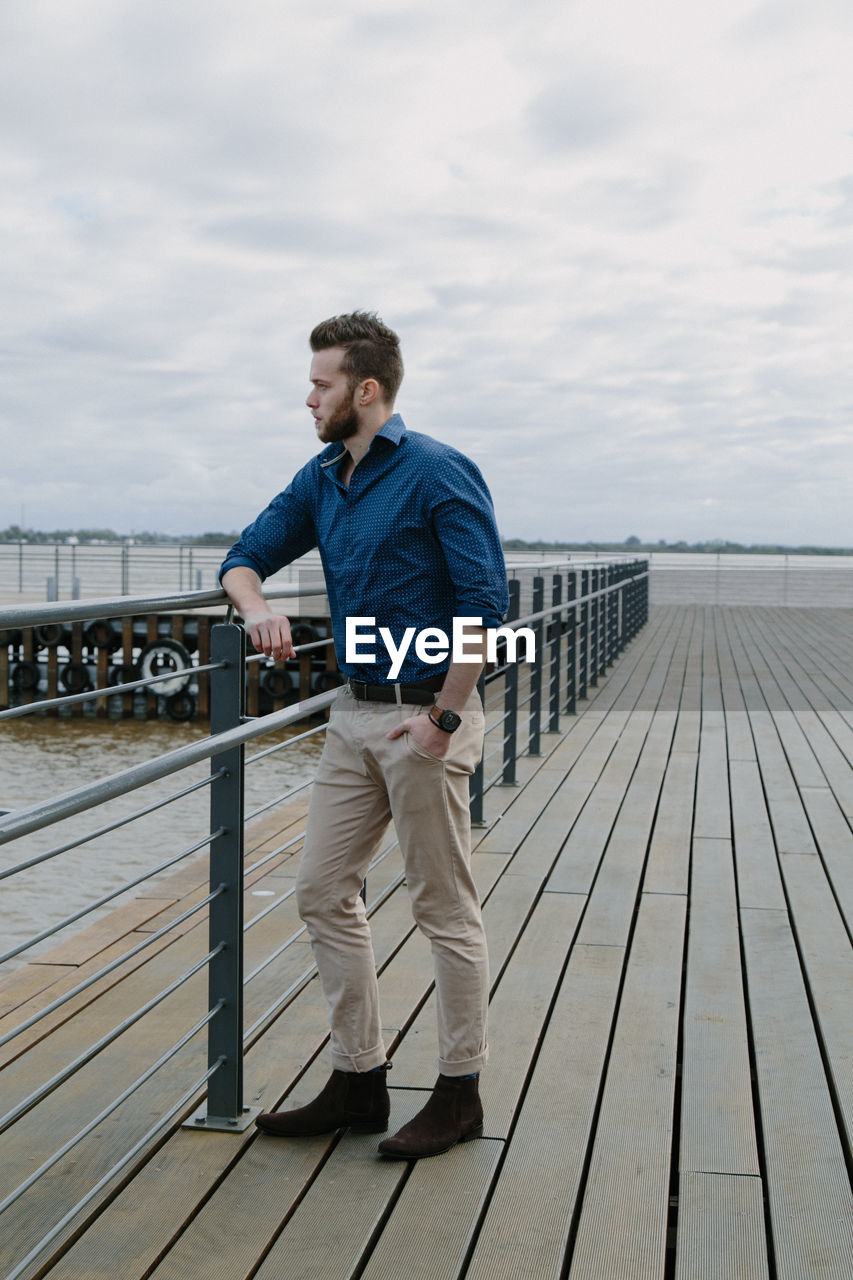 Young man standing on pier against sky